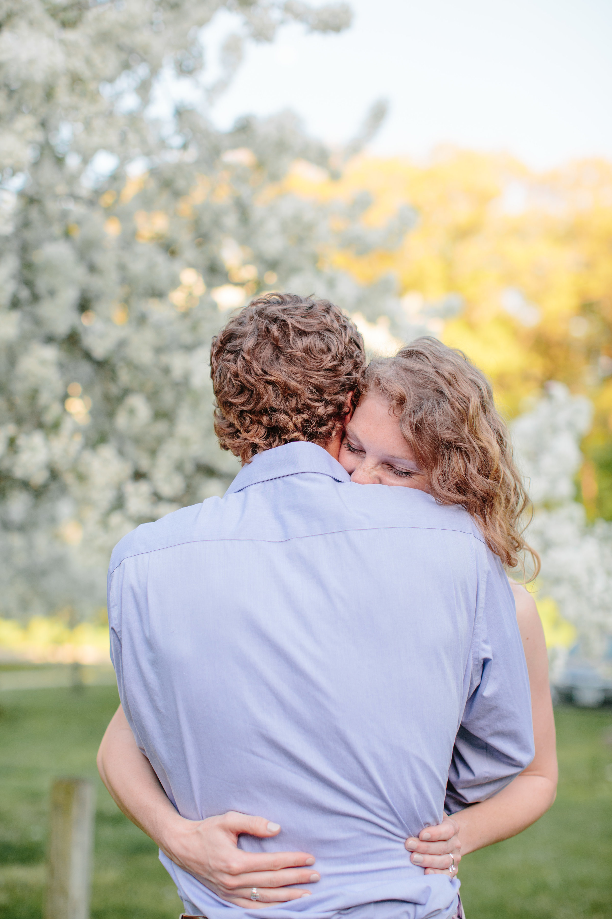 fiance hugging her groom to be in park