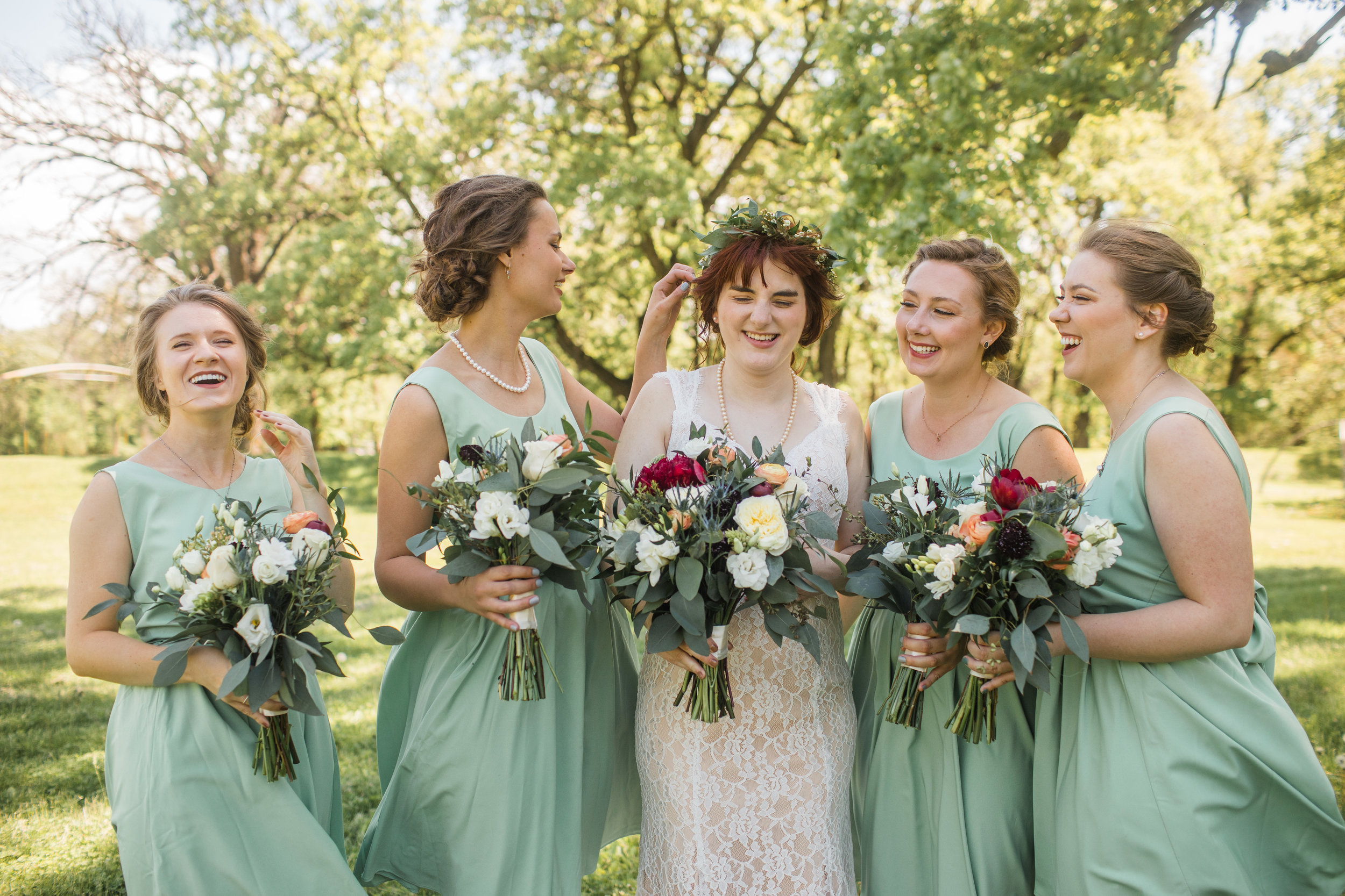 bridesmaids fixing and laughing with bride during formal wedding party photos