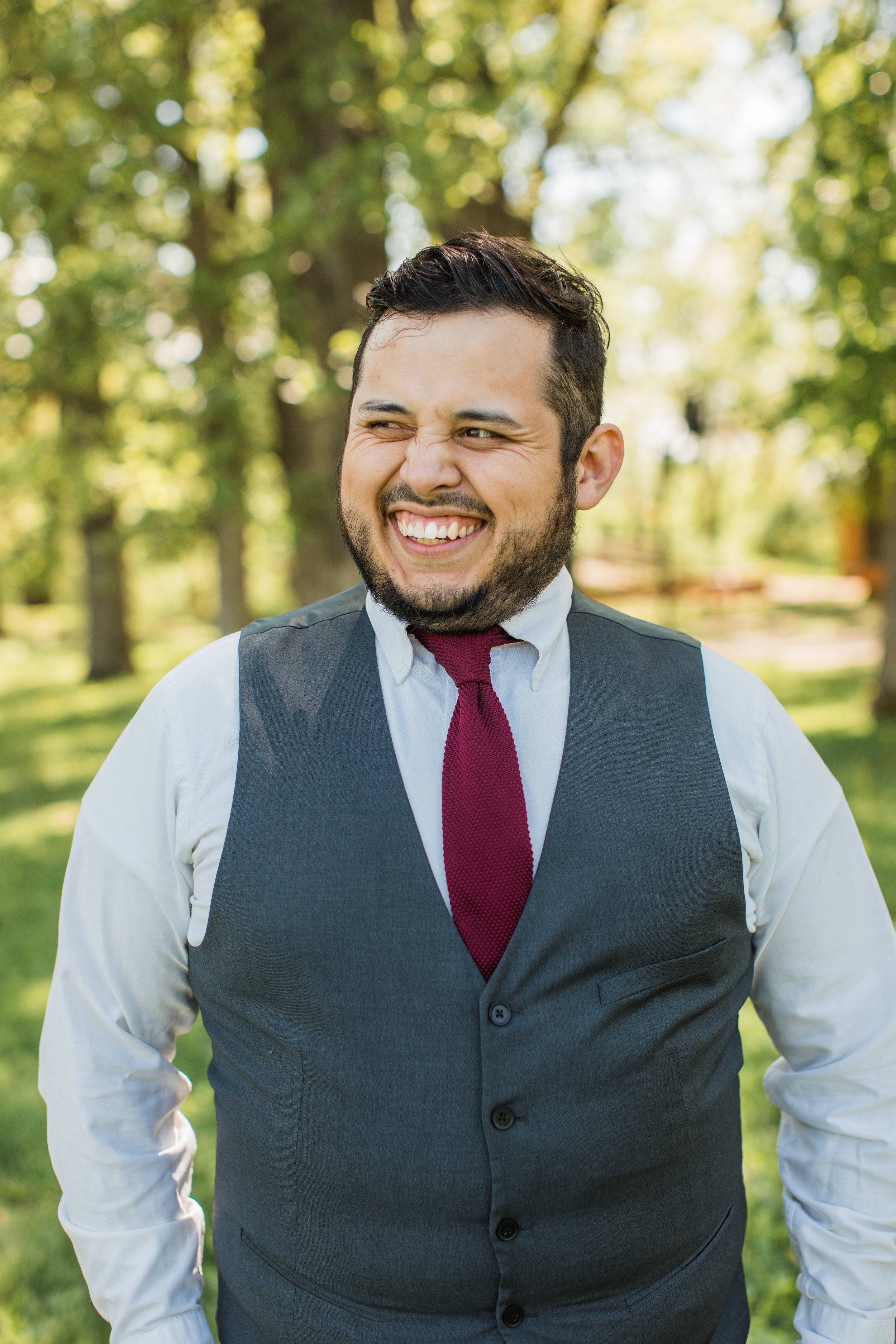 groom laughing and wearing grey vest for wedding outdoors Iowa des moines photographers