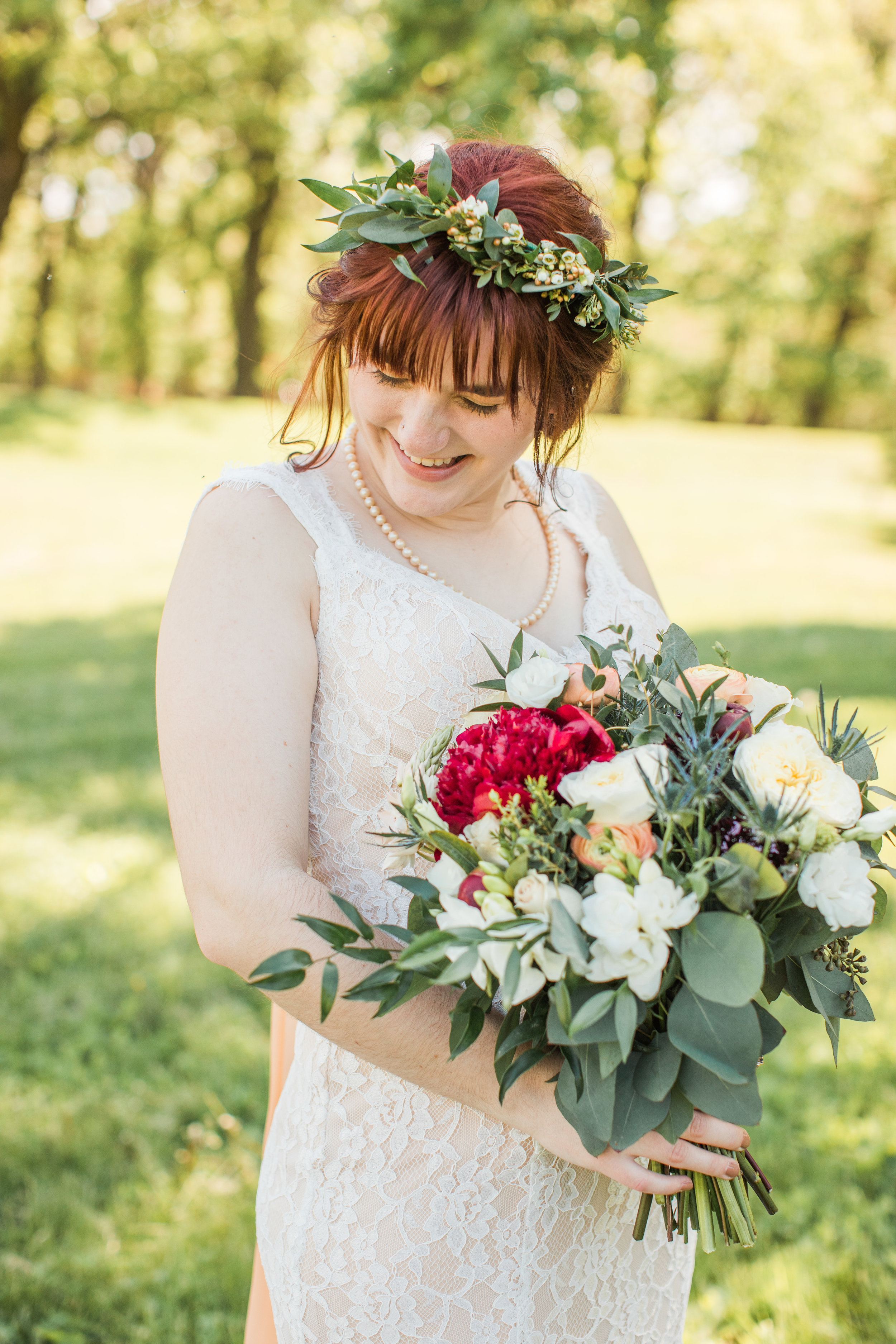 bridal portraits outside with flower crown and large colorful bouquet and wearing lace wedding dress