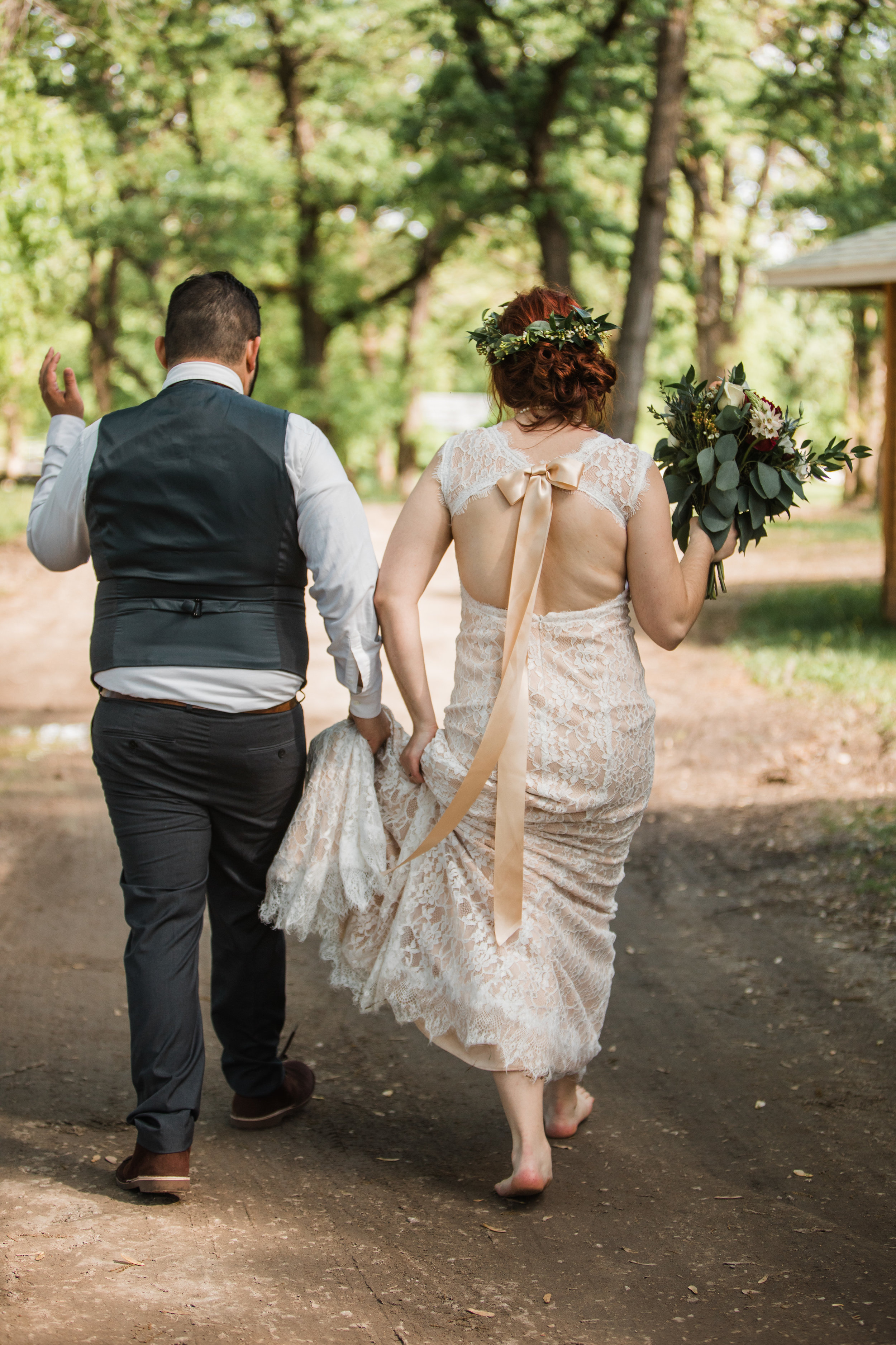 barefoot bride walking with new husband and flowers