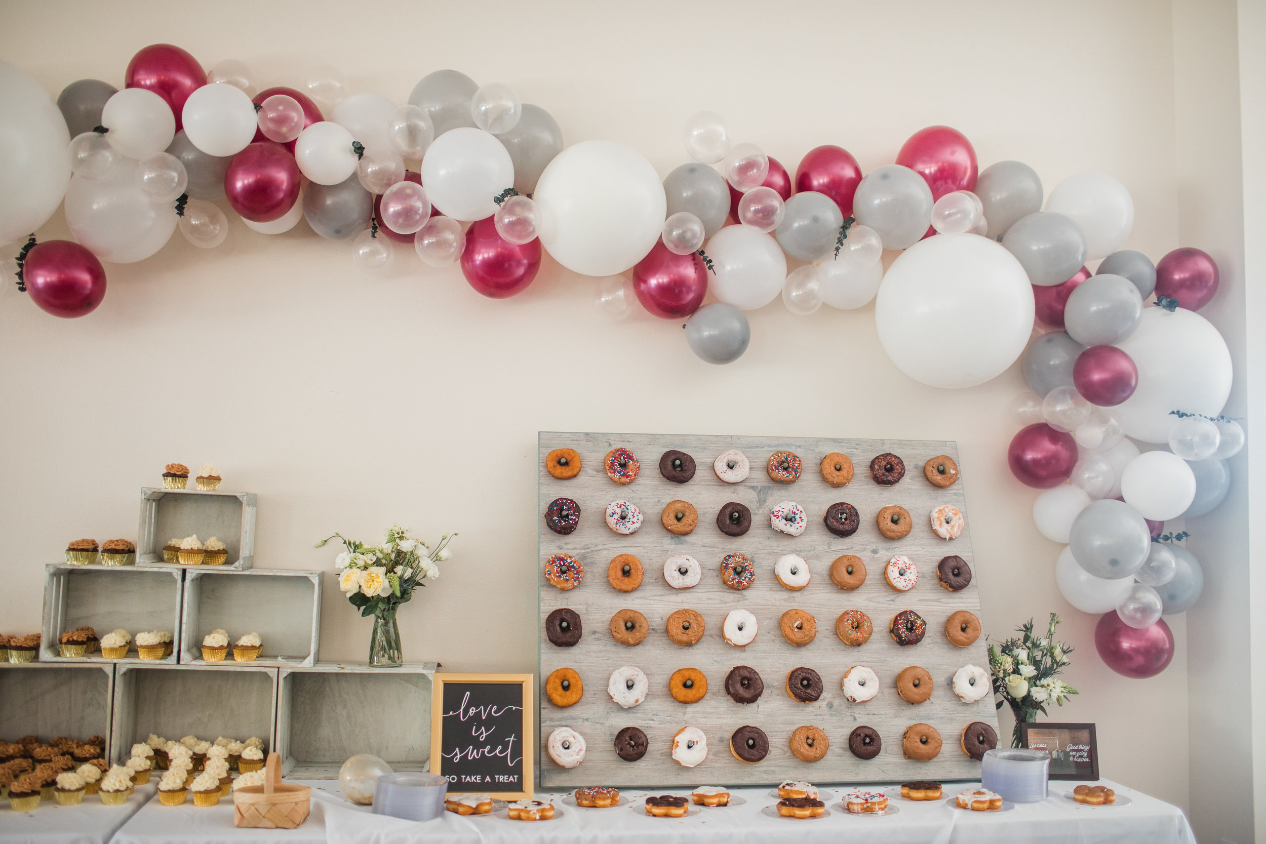 wedding reception decor balloon arch donut board and cupcakes with flowers