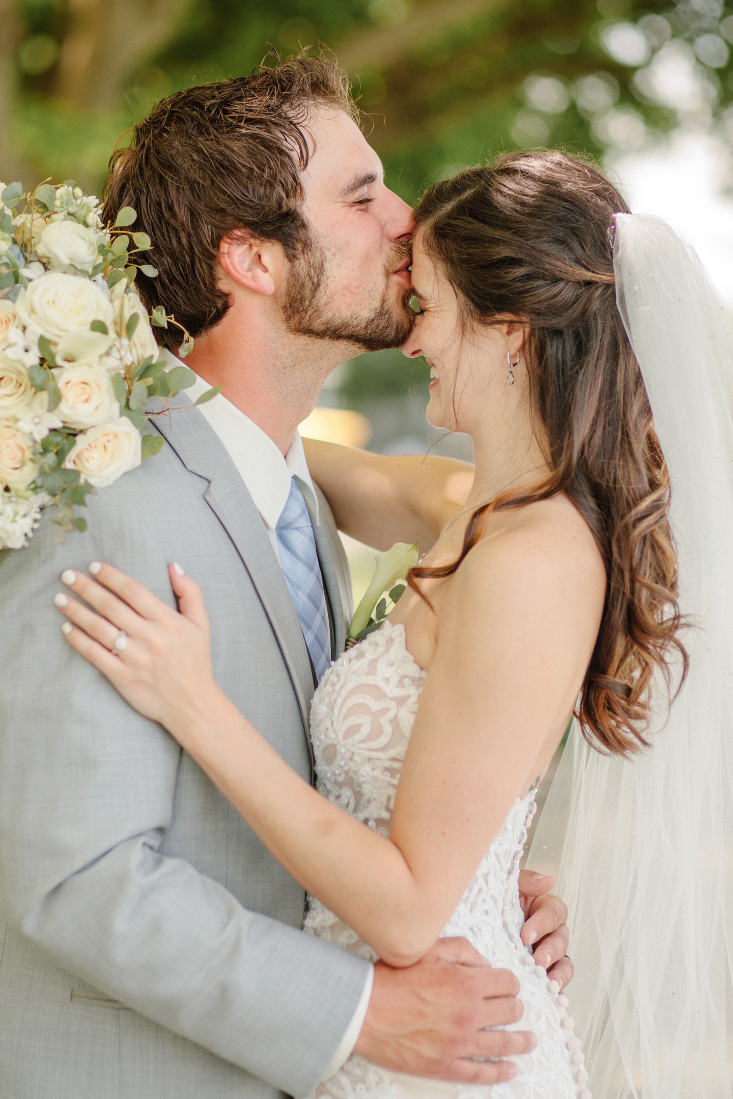 groom kissing bride on forehead and laughing together wedding day
