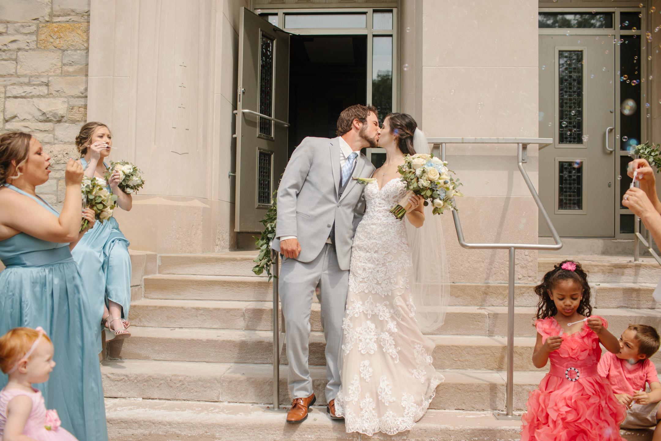 kissing outside the church sioux city wedding photos
