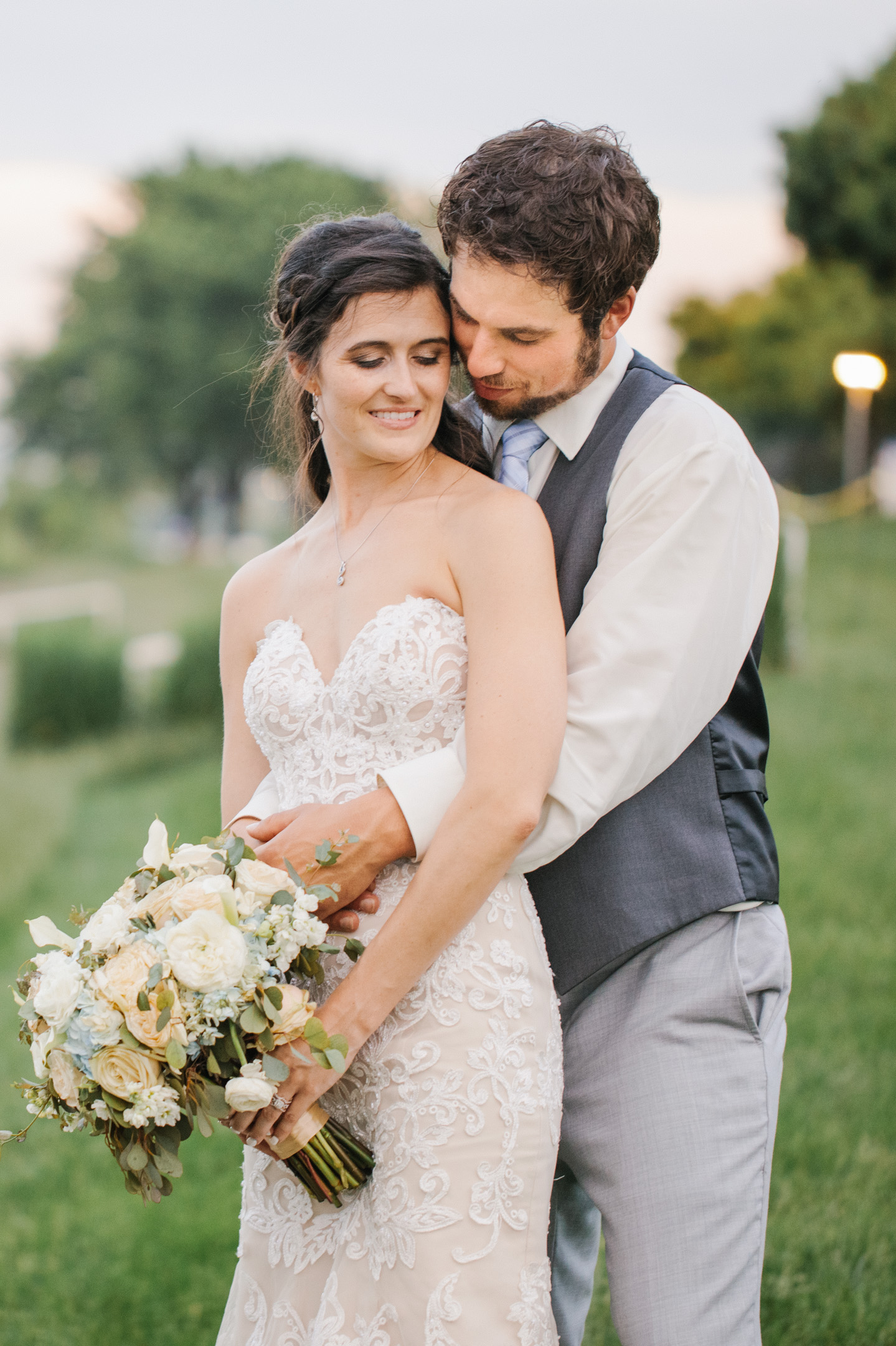couple hugging in wedding outfits lace dress and holding flowers smiling des moines iowa parks