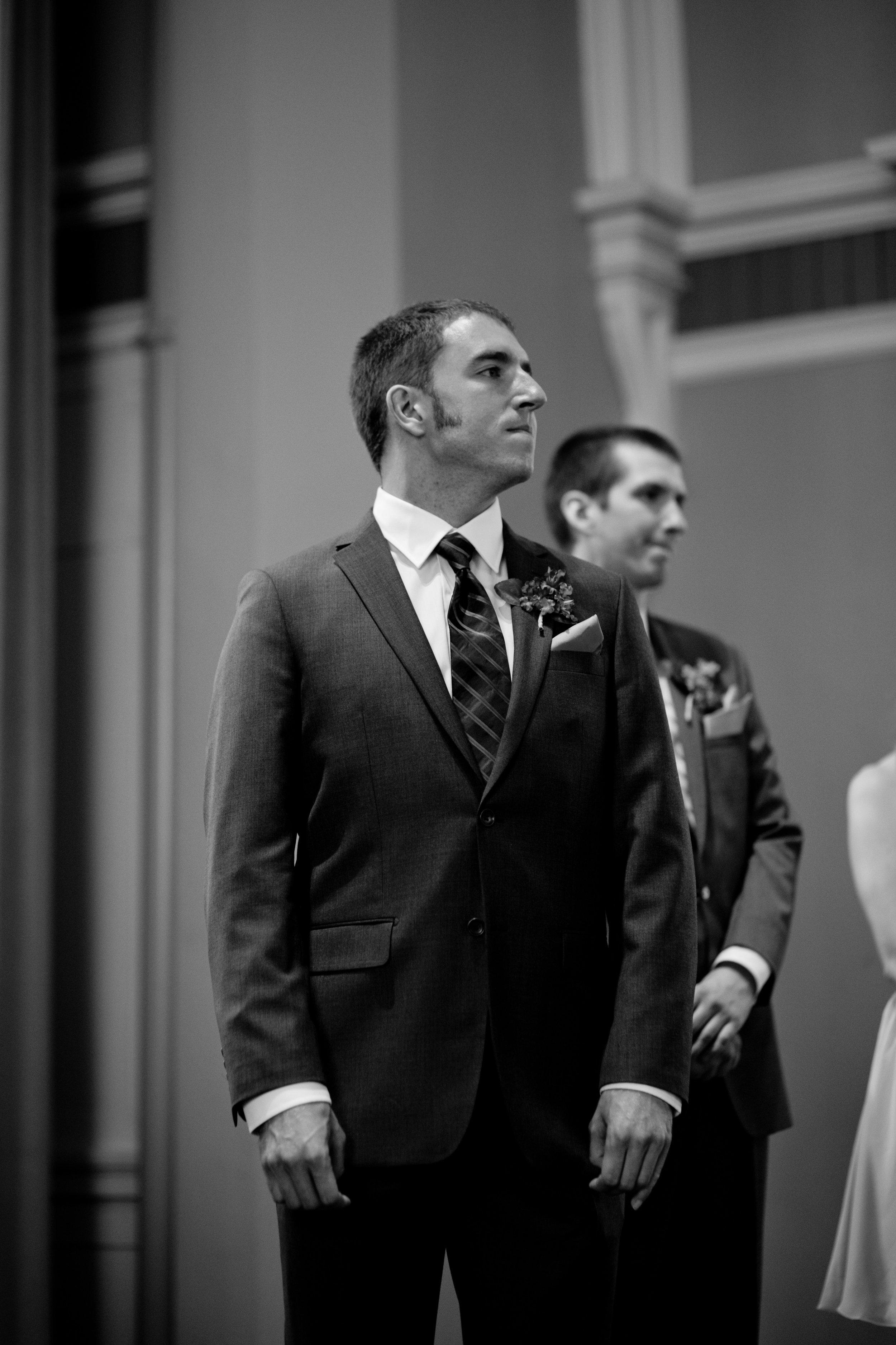 bride walking down aisle grooms face
