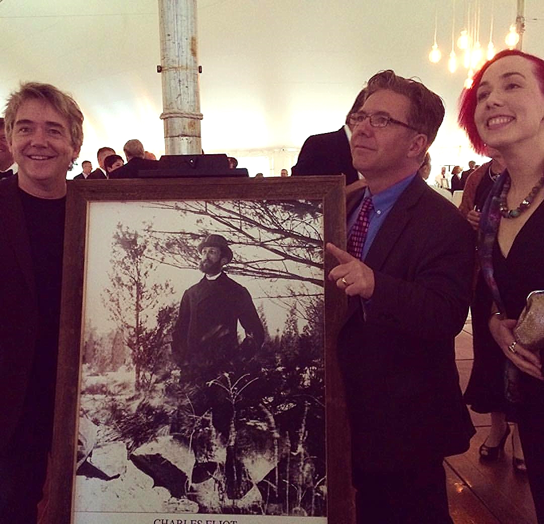 Peter, Paul and Julia stand with a picture of Charles Eliot.