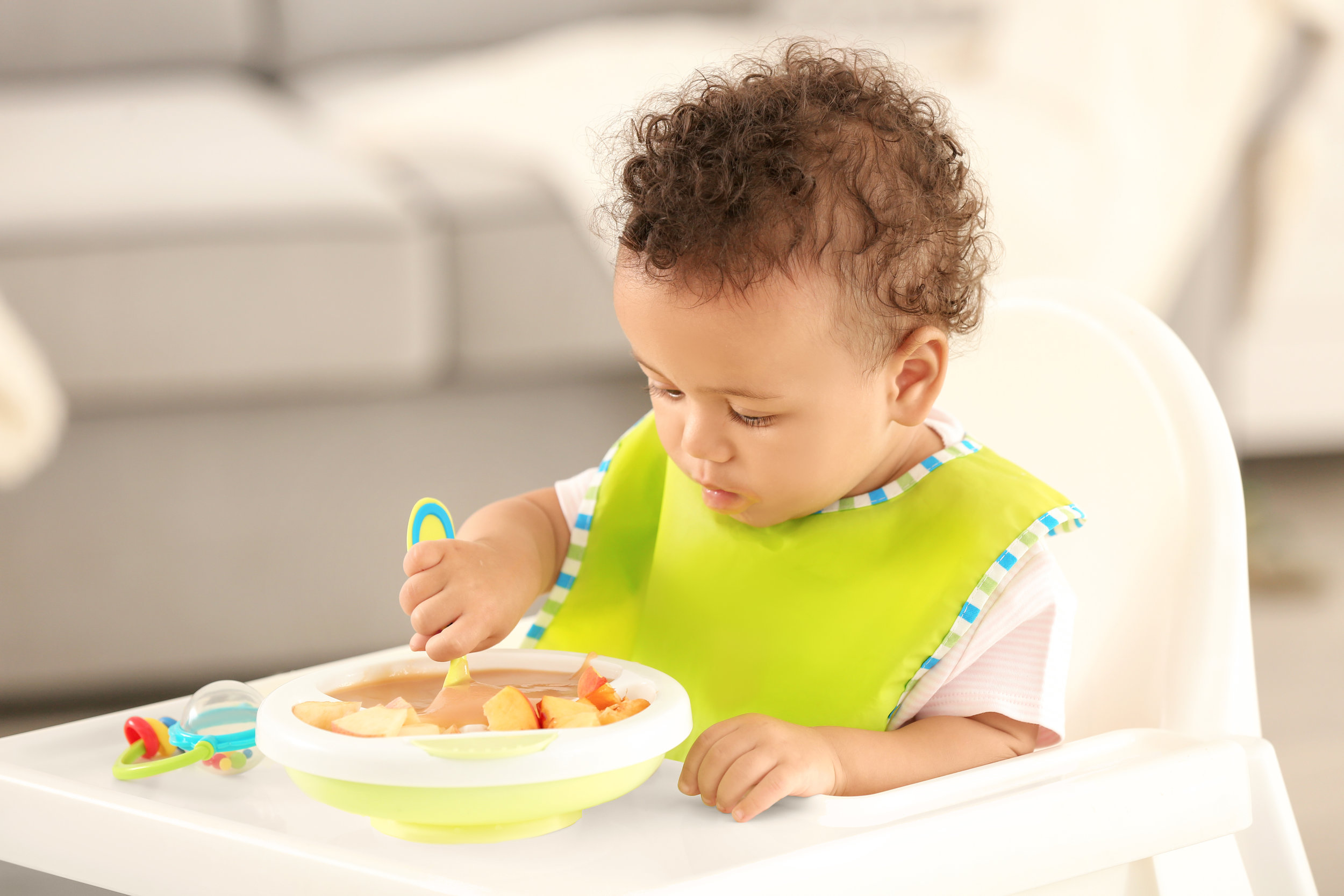 Little baby eating fruit puree indoors