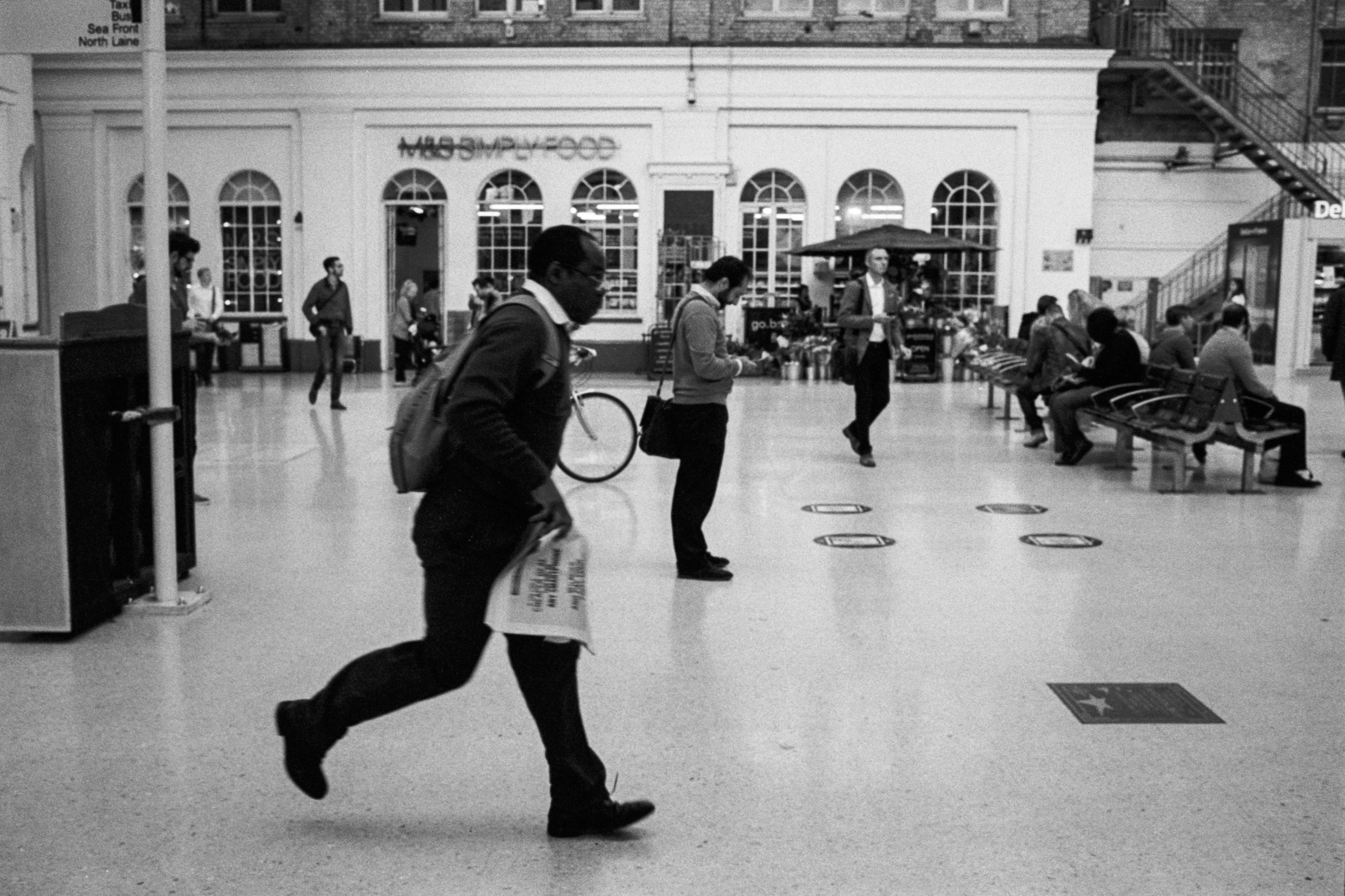 At Brighton station early in the morning. A man runs for the train clutching a newspaper. In the background people sit and wait, watching the train departure boards. A man carrying a black laptop bag looks engrossed in his phone.