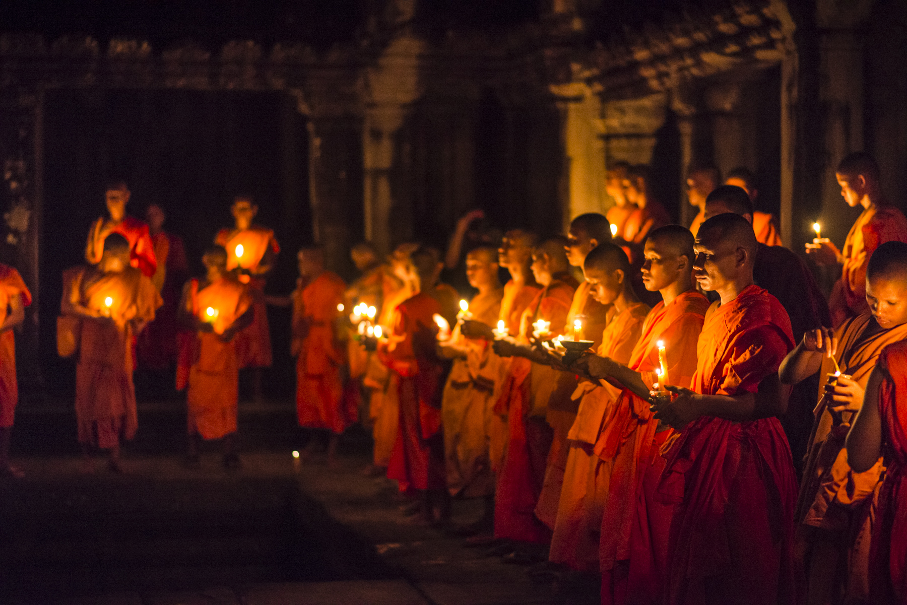Monks holding candles as they gather in the Gallery of 1,000 Buddhas at Angkor Wat.