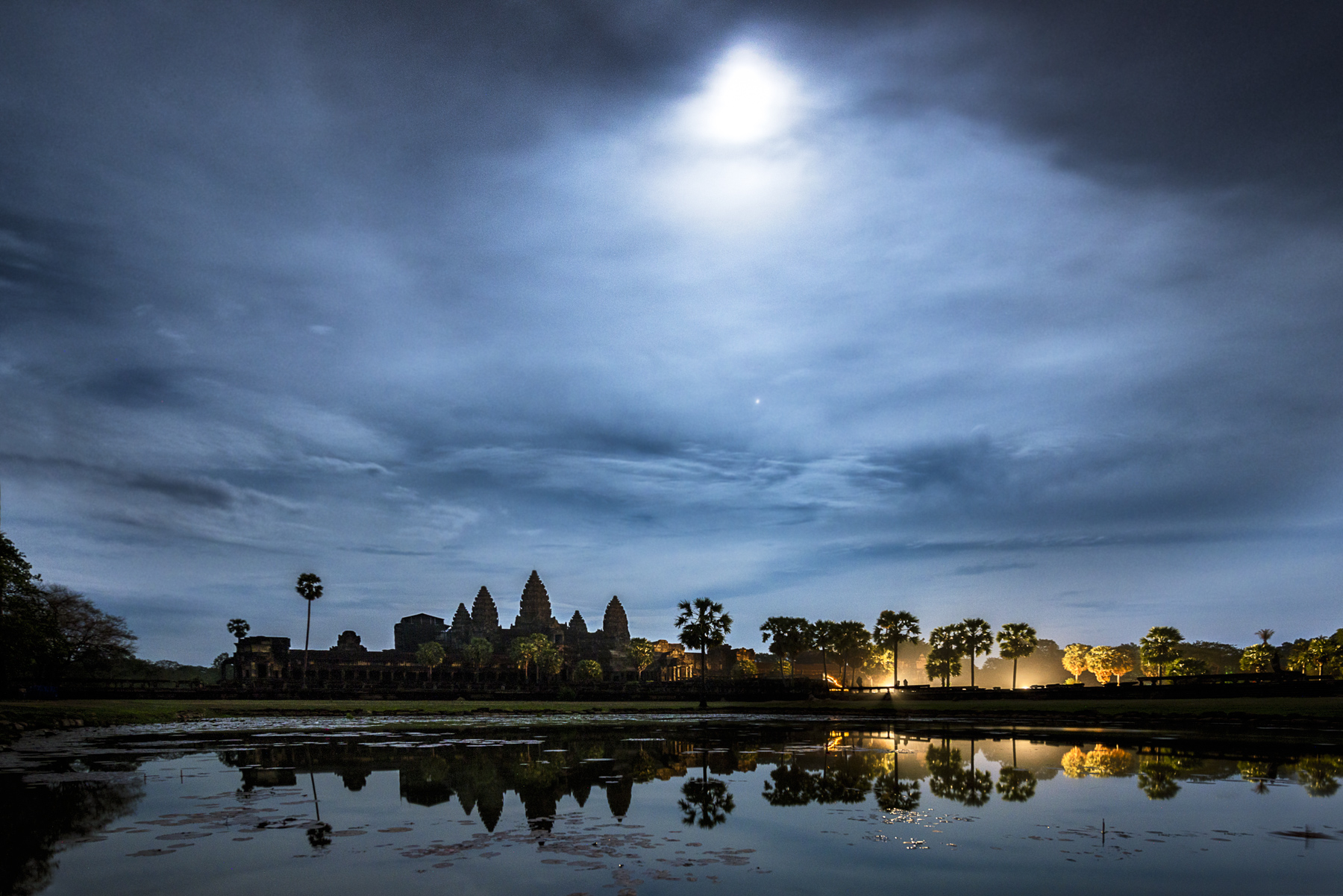 Angkor Wat reflecting in the surrounding pond beneath the light of the full moon. After the candle procession and meditation the families gather to celebrate their young children being blessed by nuns and monks for the first time as they begin their spiritual journey.