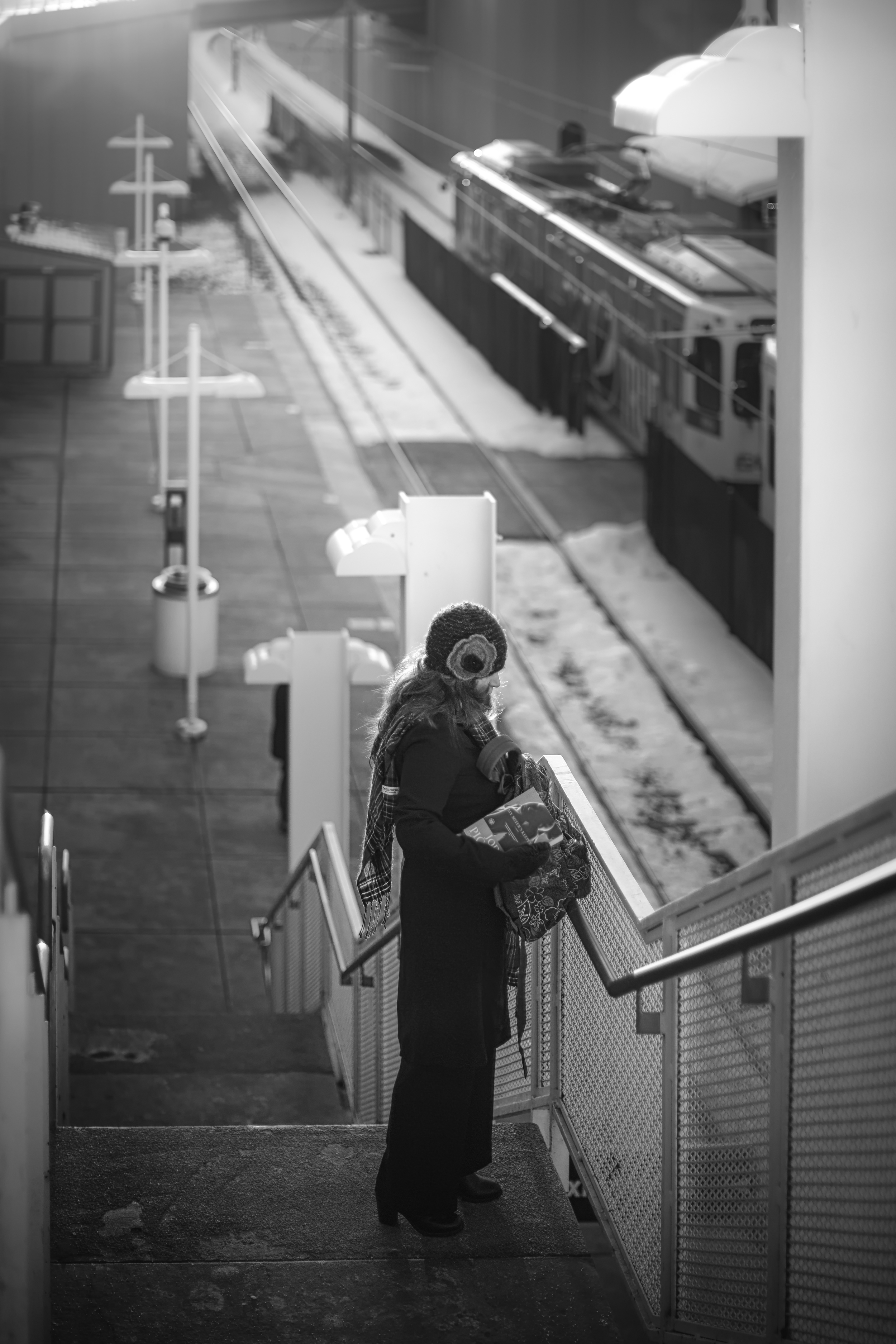 A women standing on the stairs at the train station.