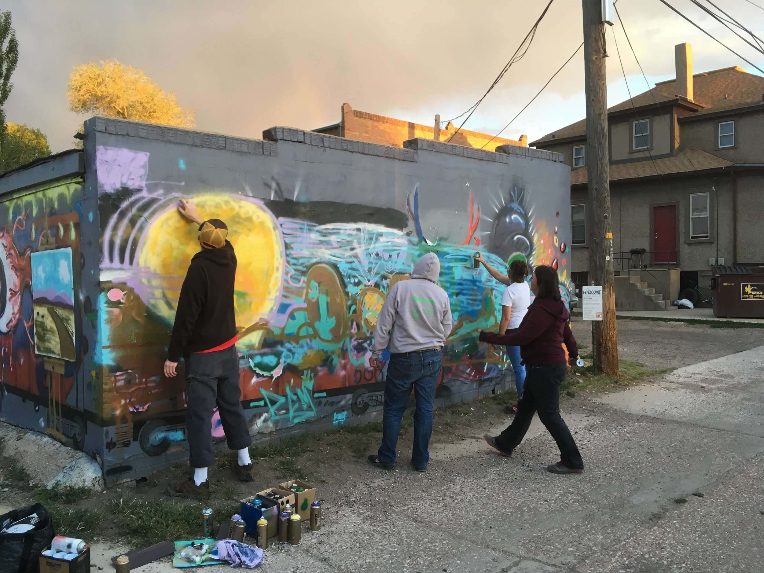 Artists work on a group mural at the end of Dan Toro's spray paint workshop in Sept 2018. Mural inspired by Vedauwoo.