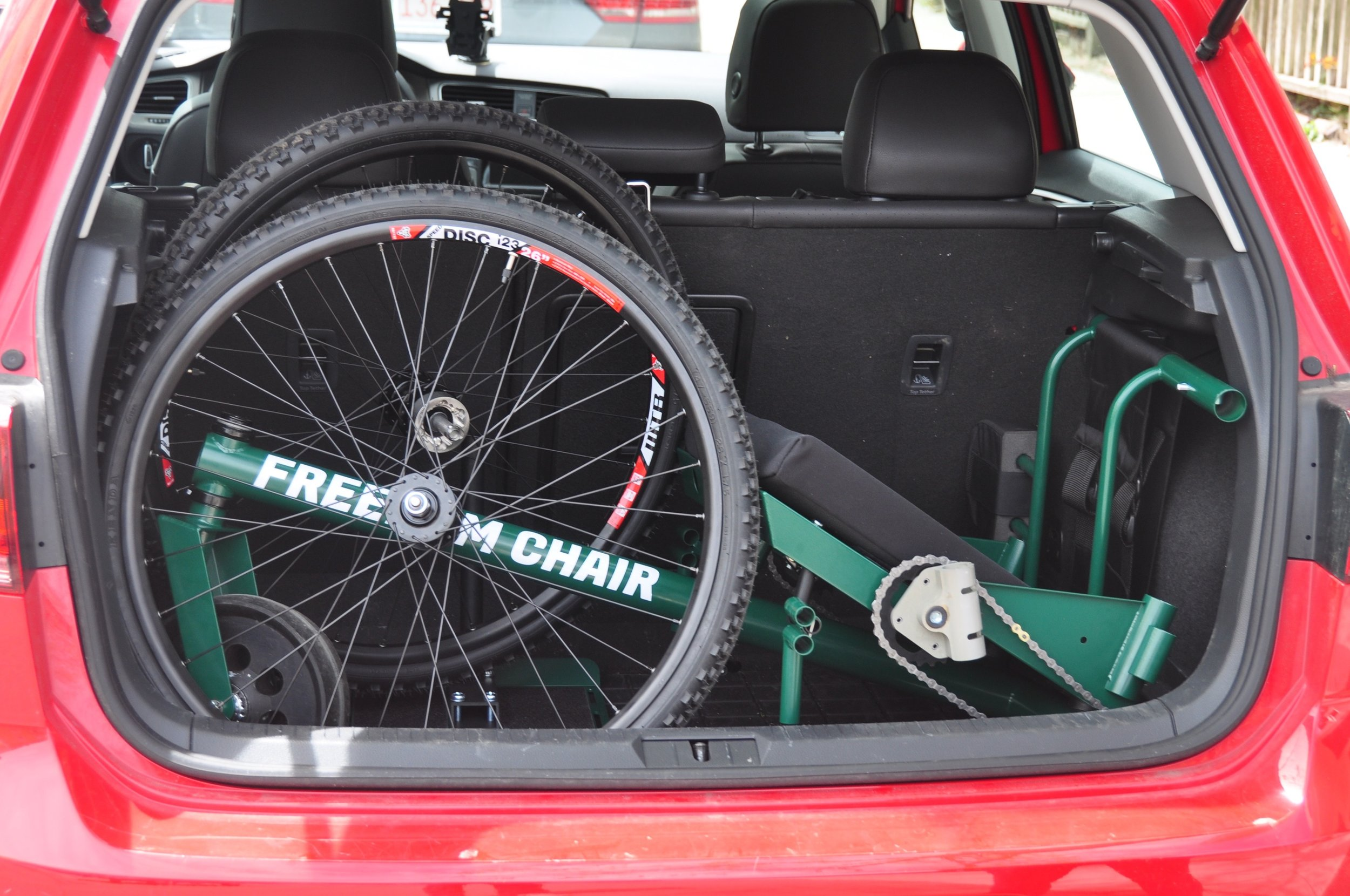 Transporting the disassembled GRIT Freedom Chair in the trunk of a hatchback.