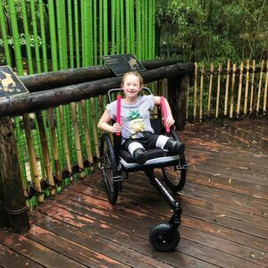 """When Lilly was born, her legs were affected by a rare muscular condition. At six years old, she had both of her legs amputated above the knees. Her original prosthetics were uncomfortable and difficult to remove and maneuver and she now uses a GRIT all-terrain amputee wheelchair to explore and adventure.    """"I got to control the terrain instead of the terrain controlling my advantage! Wet and slippery zoo trails you got nothin on me now!"""""""