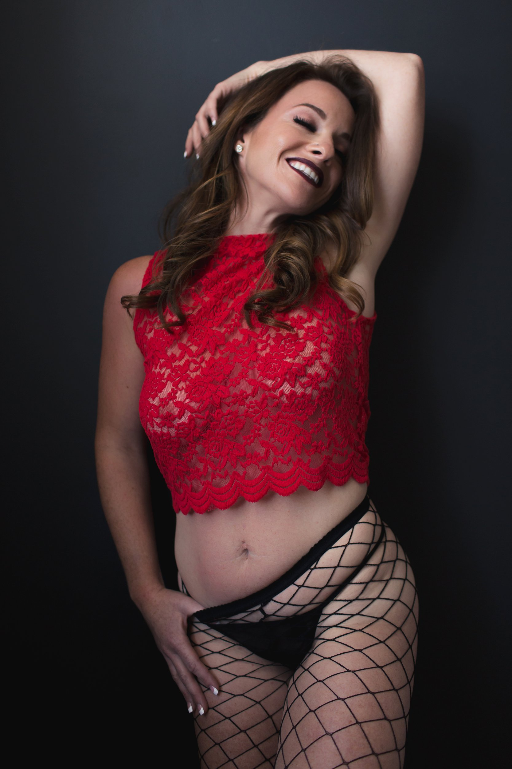 Woman in red lace top and black fishnet stockings smiling