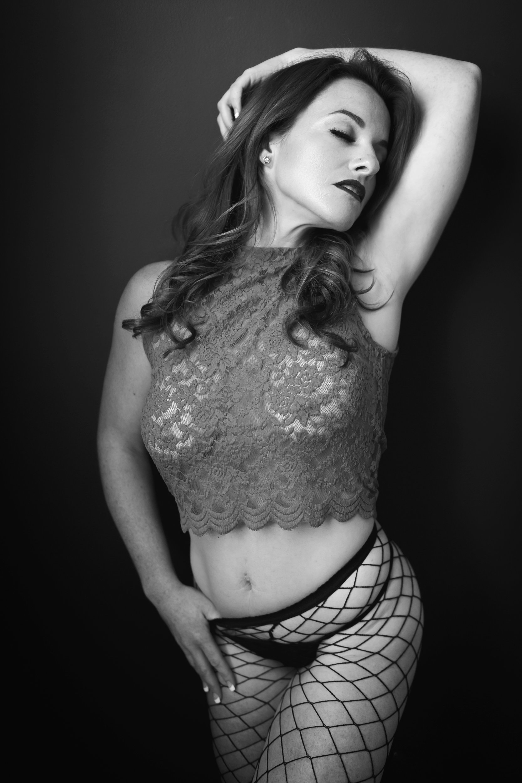 Black and white photo of woman in lace top and fishnet stockings
