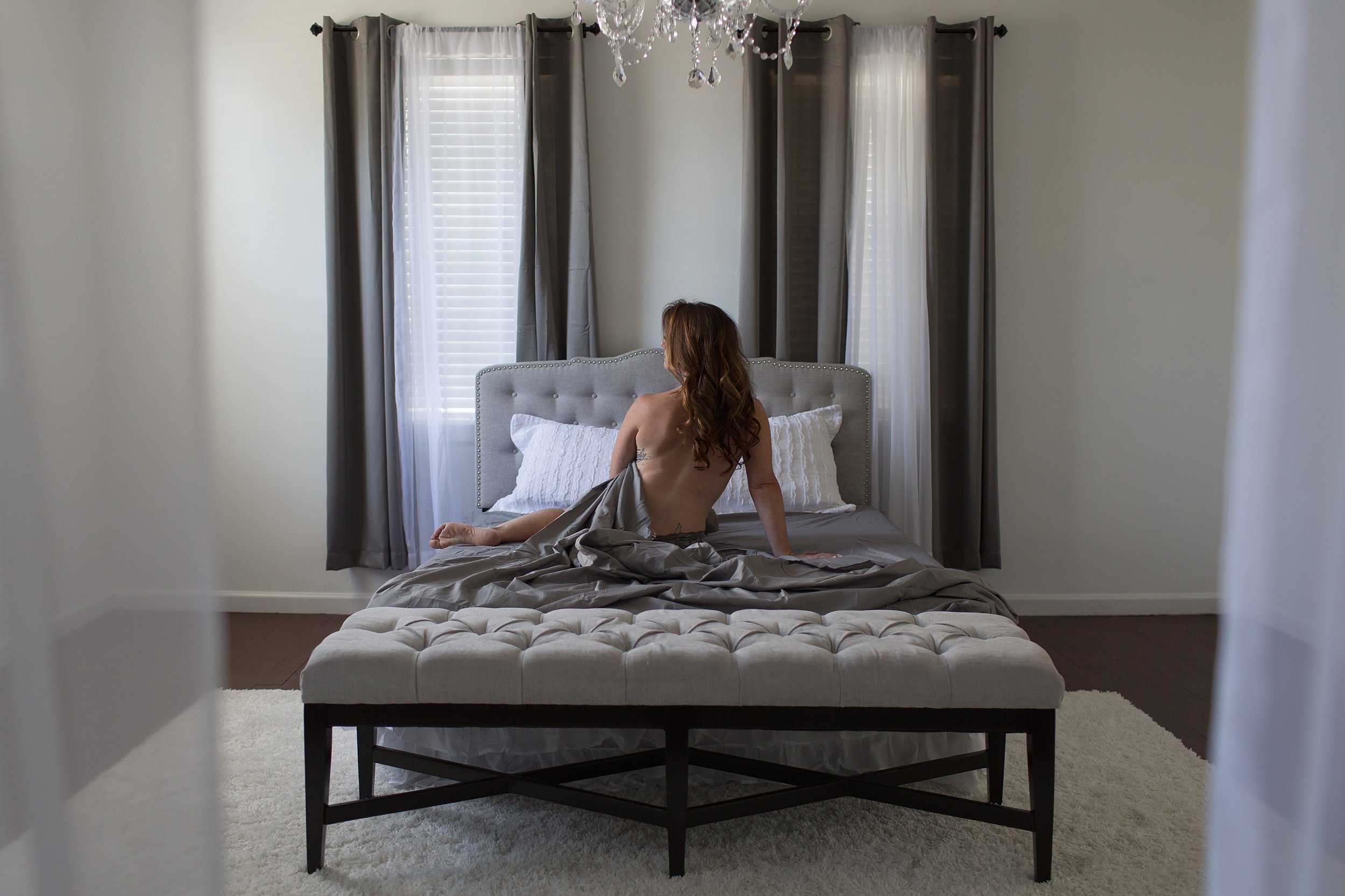 Woman sitting on bed in pretty room with gray sheets, tufted headboard, chandelier