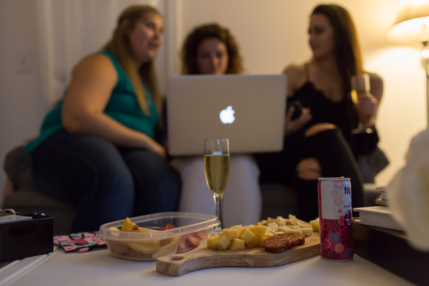 Drinks and snacks laid out on a table in front of women looking at a computer
