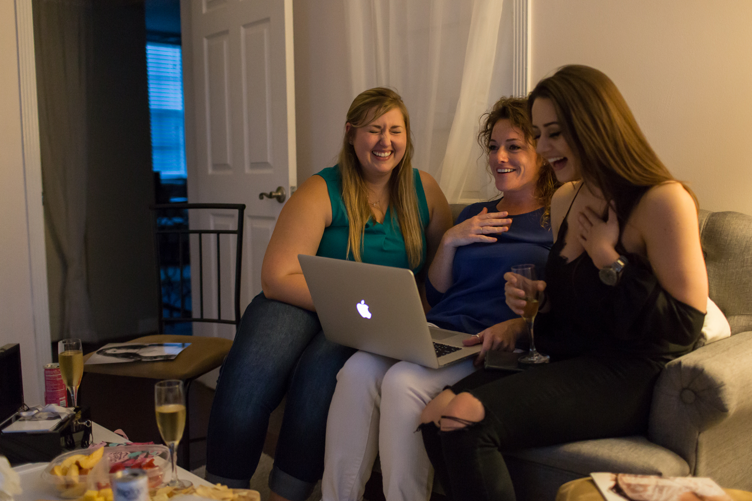 Three girls laughing together on couch