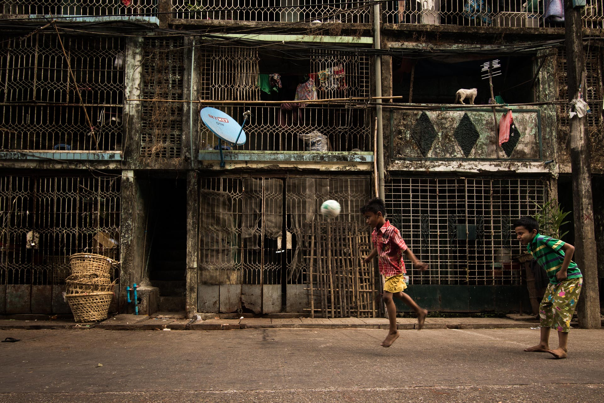Children playing ball in the streets of downtown Yangon. Myanmar