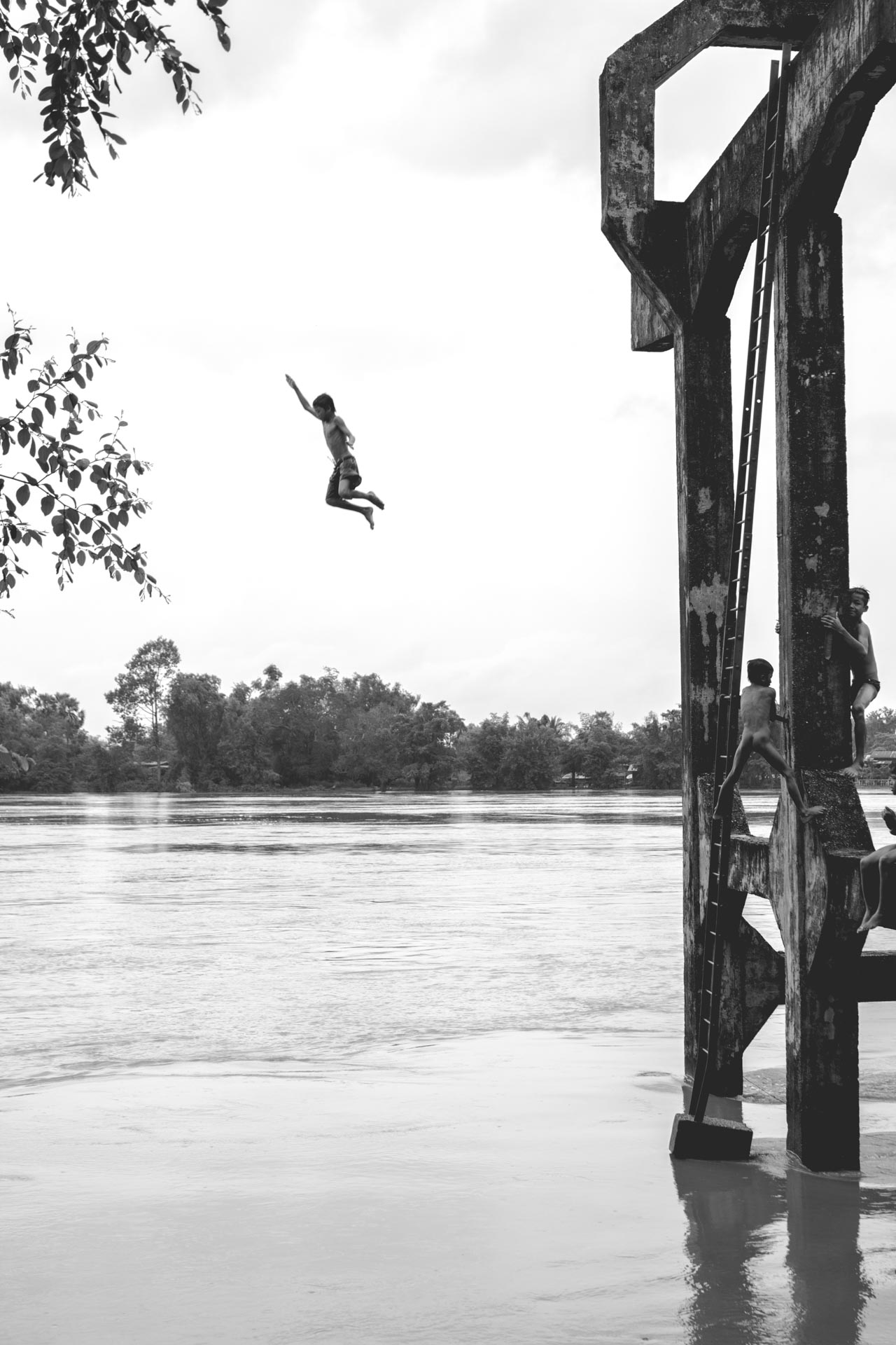 Children jumping off an old aqueduct into the Mekong river at Don Det. Laos