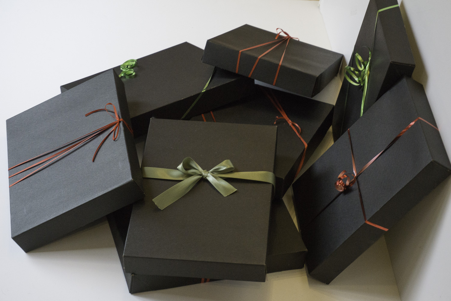 Simple shirts boxes can hold 8 x 10 inch art pieces. Ribbon makes a nice finishing touch. These tuxedo striped shirt boxes are available from Nashville Wraps. Each box cost $0.51.