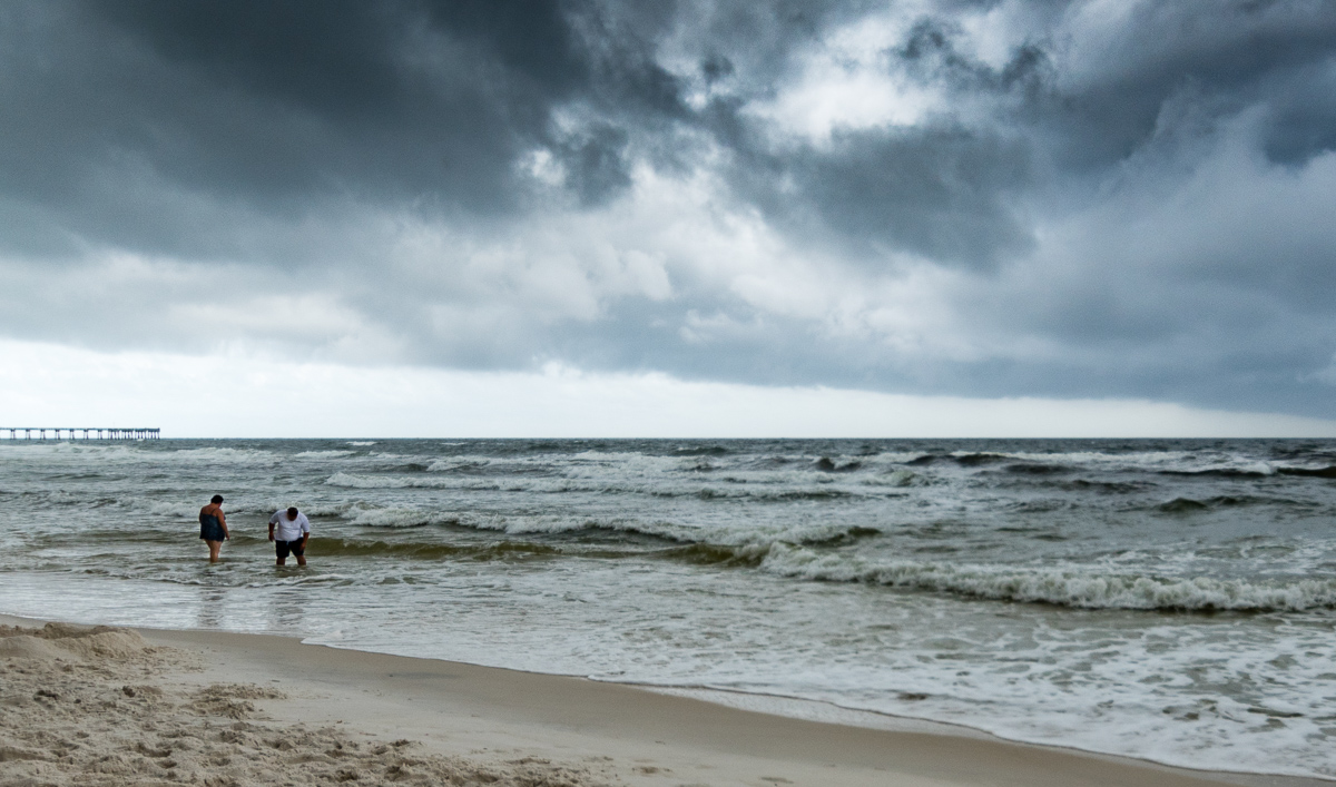 """""""Testing the fates"""". (c) Rebecca LaChance, 2016. Panama City Beach, FL.  Despite double red flags, beach patrols with loudspeakers, airplanes with banners, these folks (and many others) wandered out into the waters."""