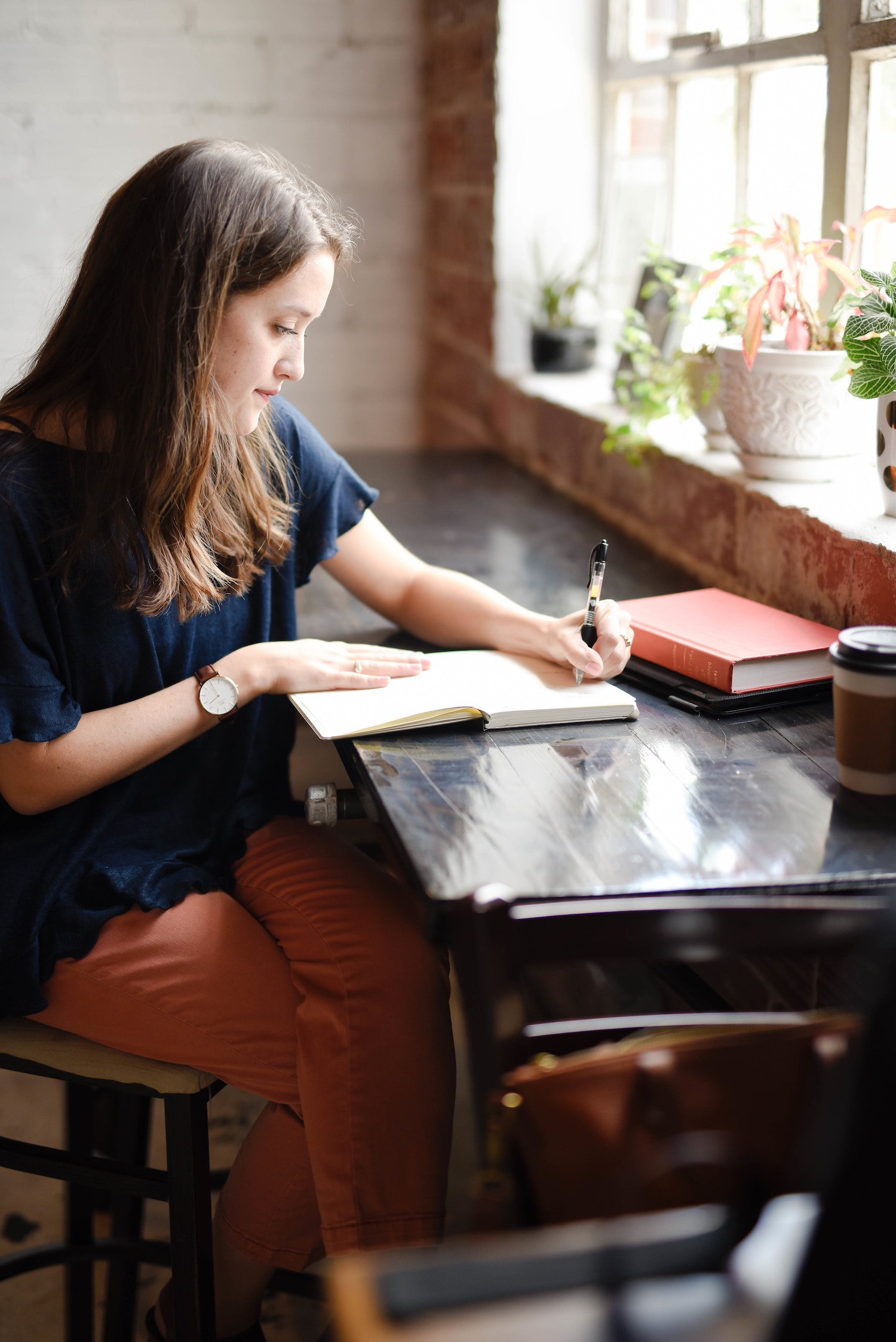 A woman sits at a bar in a coffee shop, writing in her journal