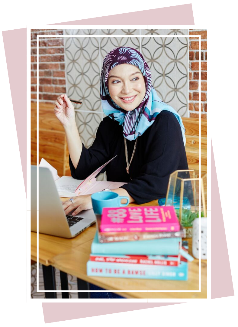 Shuhada sitting at a table writing in her journal