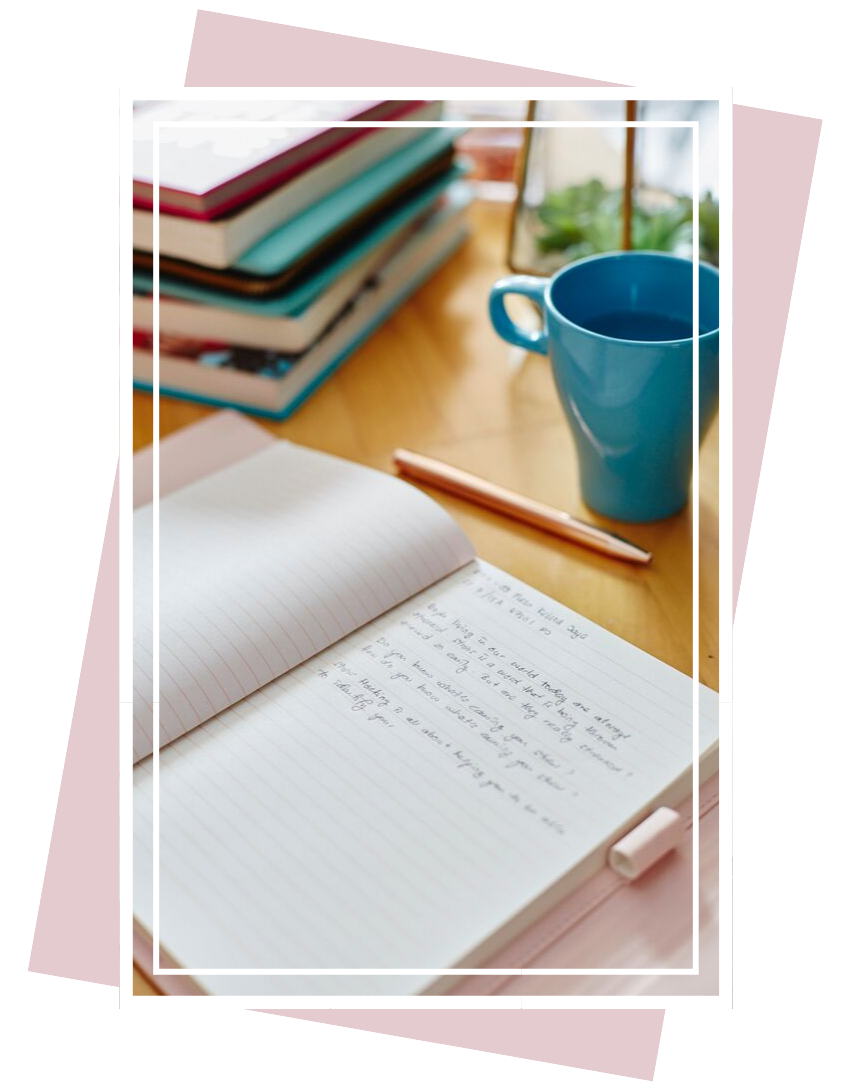 An open journal on a table with a teal coffee mug and stack of books in the background
