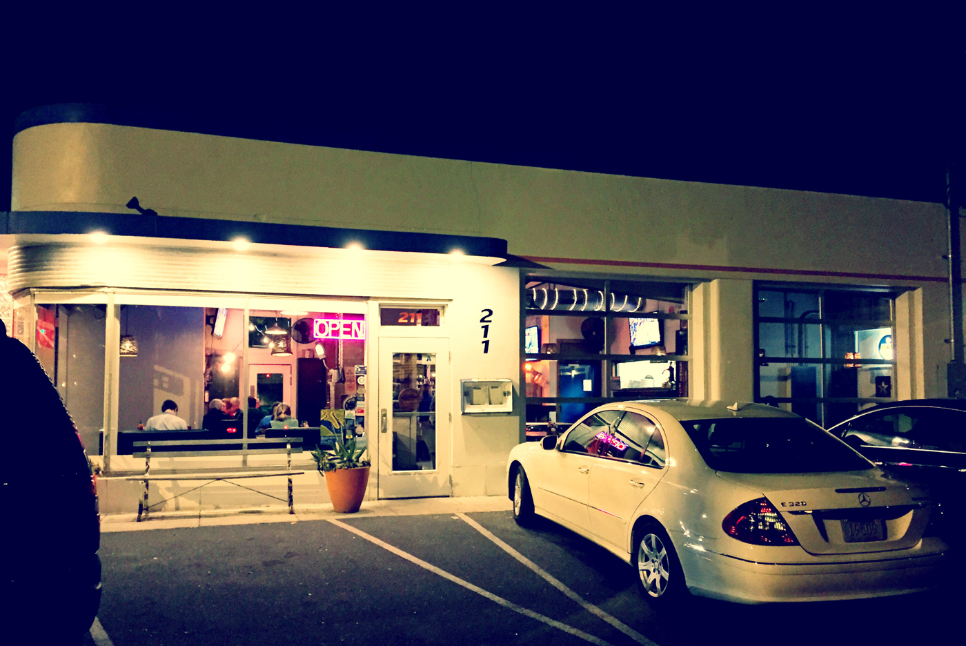 If you took out the modern vehicles, this photo could be taken from the 50's. This restaurant has that classic mid-century modern feeling. It looks like it was straight out of an Edward Hopper painting.