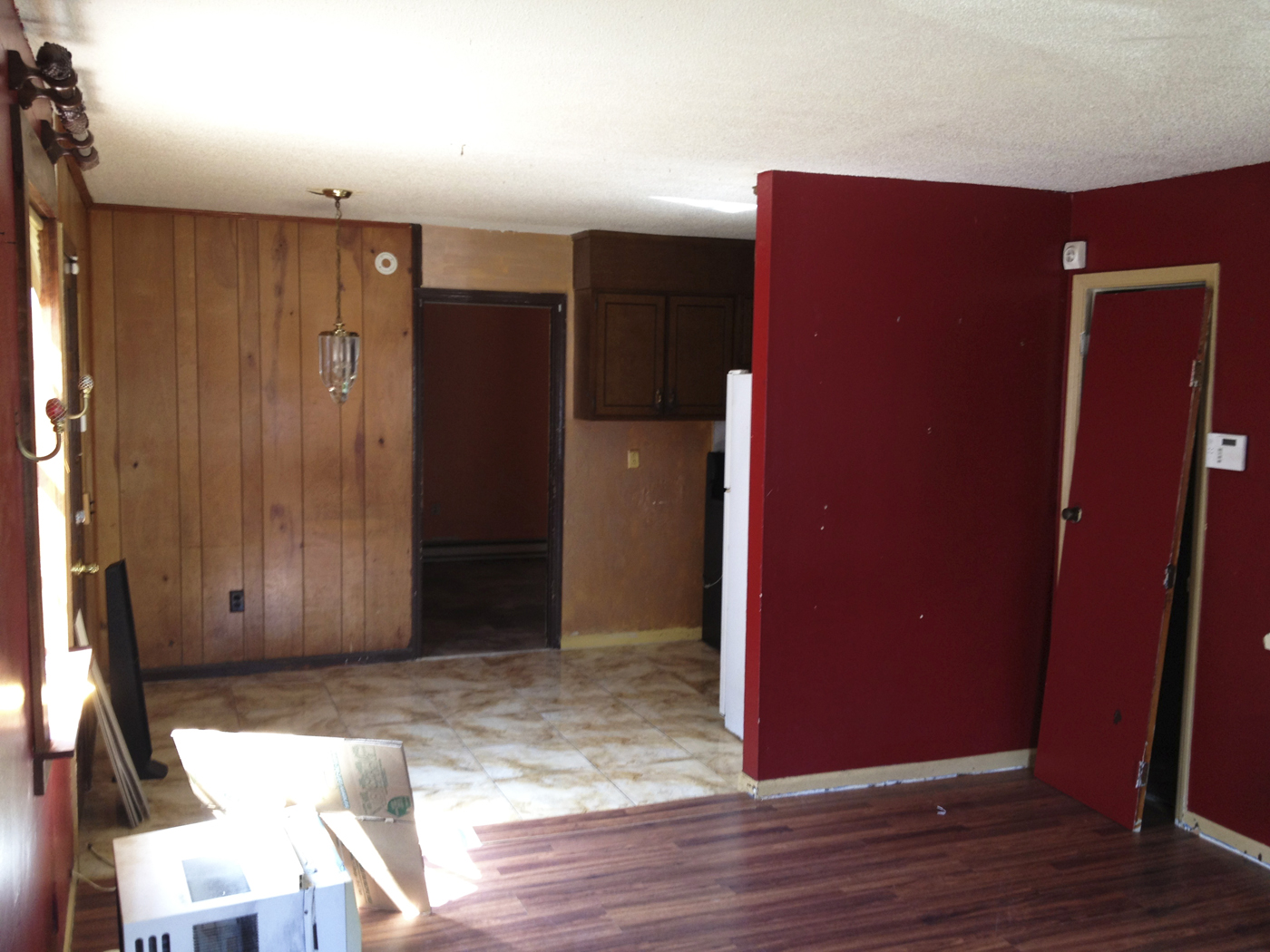 This is just bad, bad, bad, bad. The red paint, the tile and laminate floor,the wood paneling.......bad-ass light fixture though. The tiny kitchen was tucked behind that red wall.