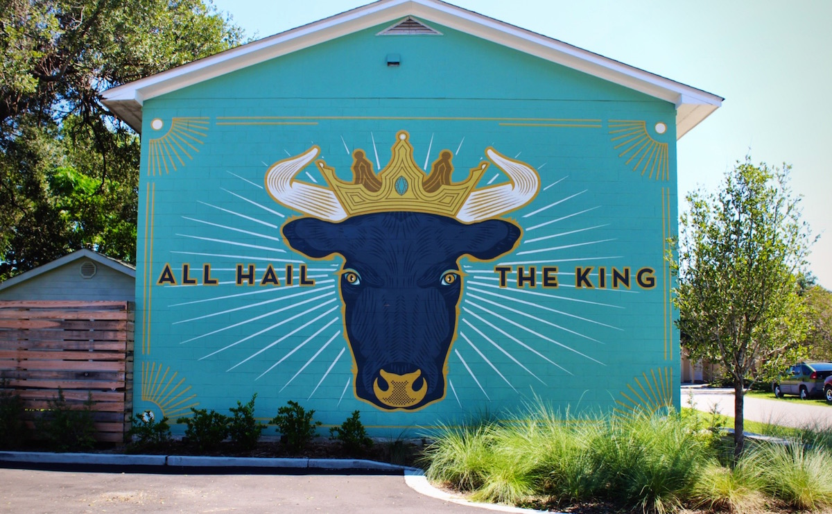 The Cow King mural is a part of the Lewis BBQ complex. Limelight Custom Sign Company painted the sign from a design by Scott Harrell.