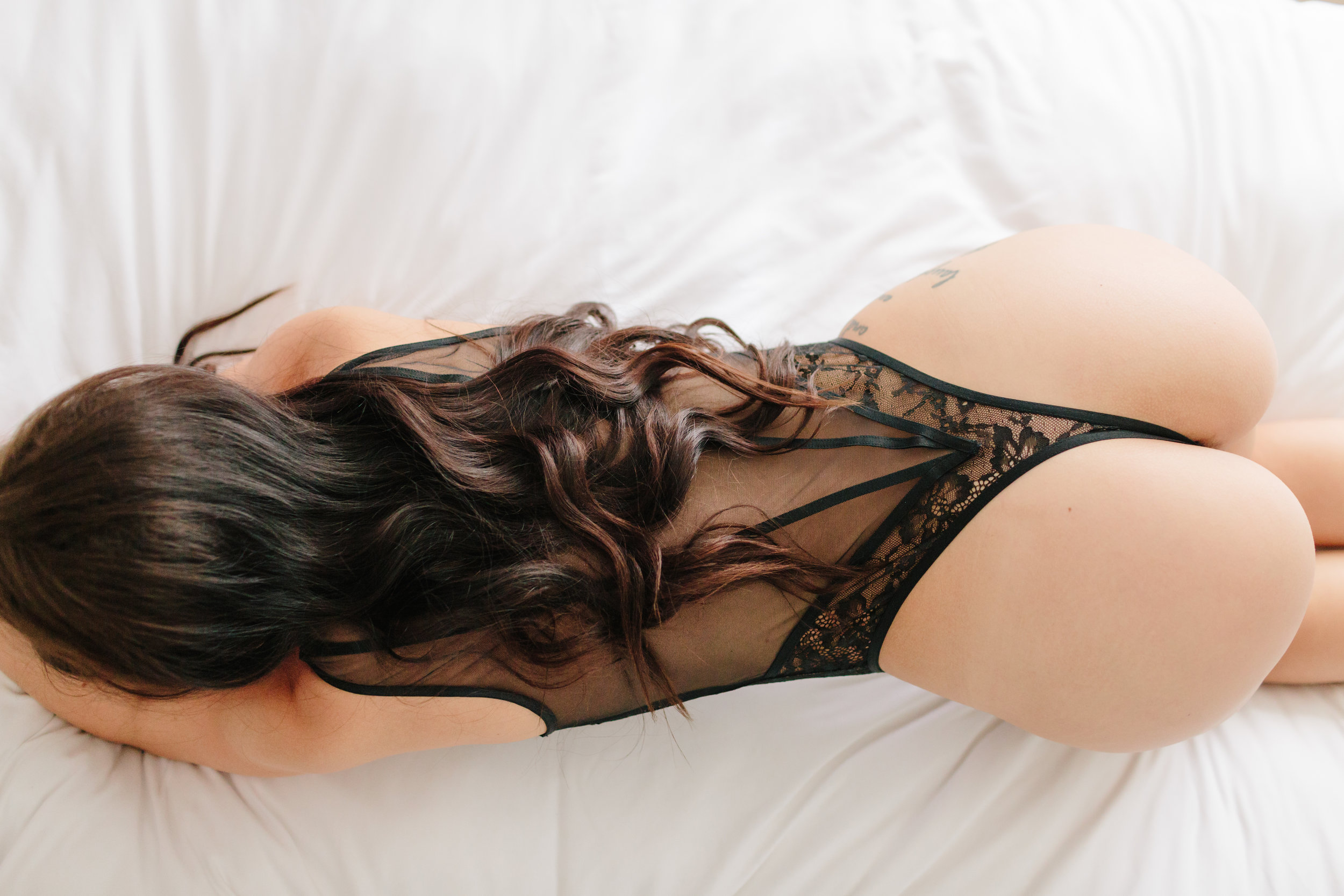 curvy woman at her boudoir session in black Lacey one piece laying in bed with white sheets