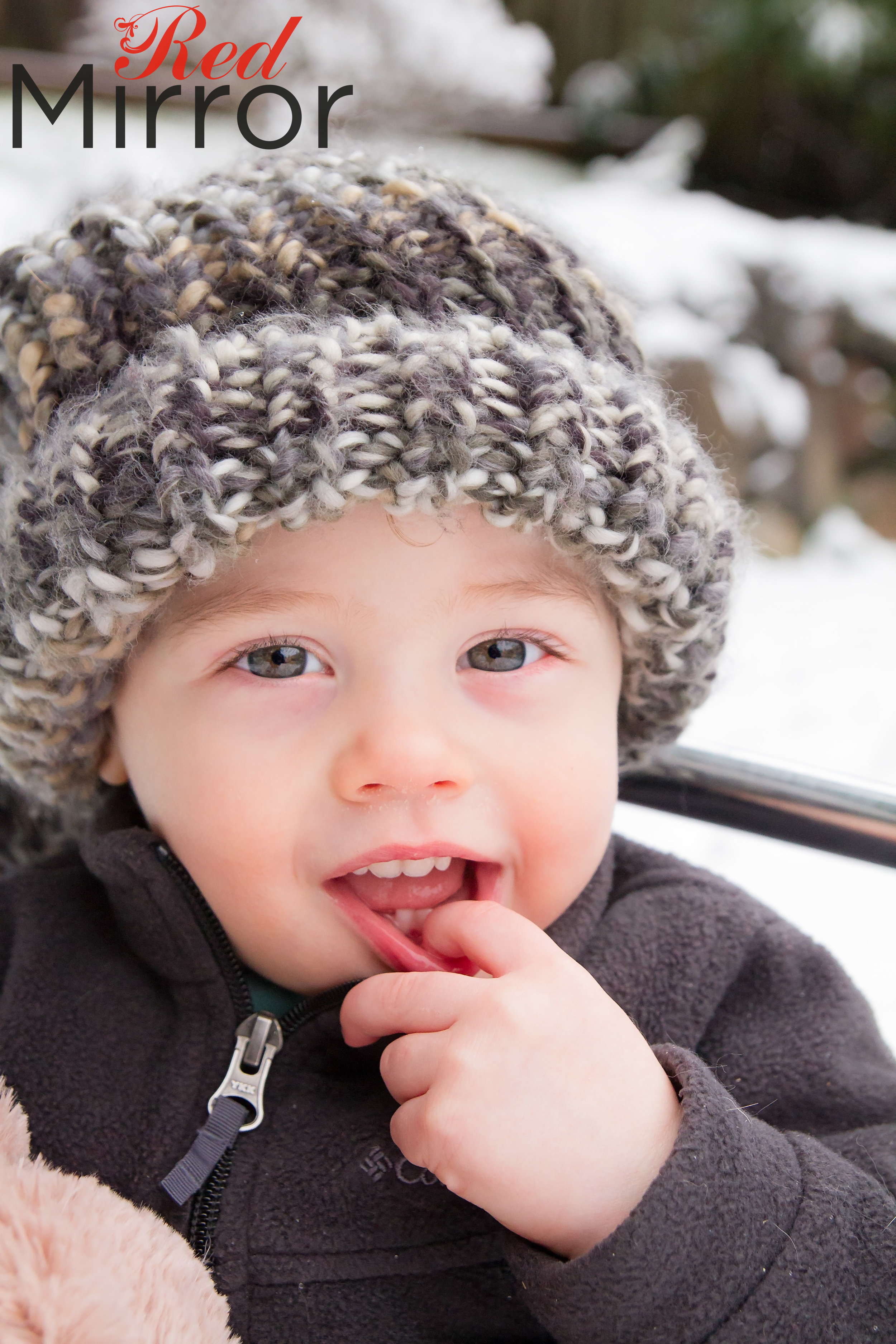 Little boy in a big wooly hat, pulling his bottom lip