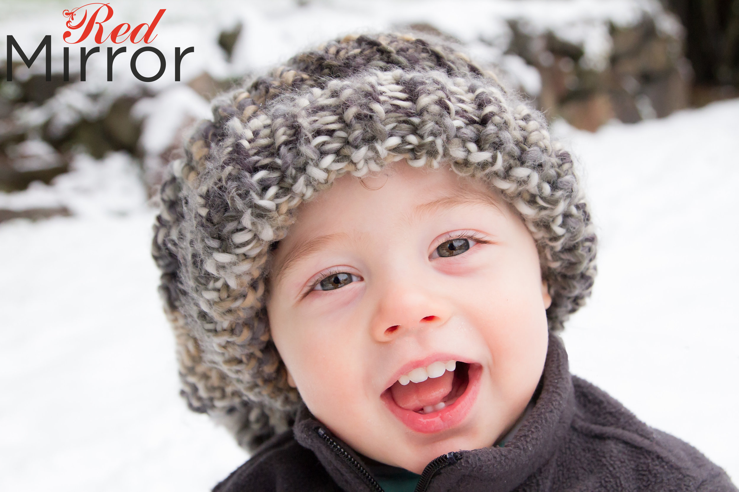 Little boy with e big wooly hat, smiling