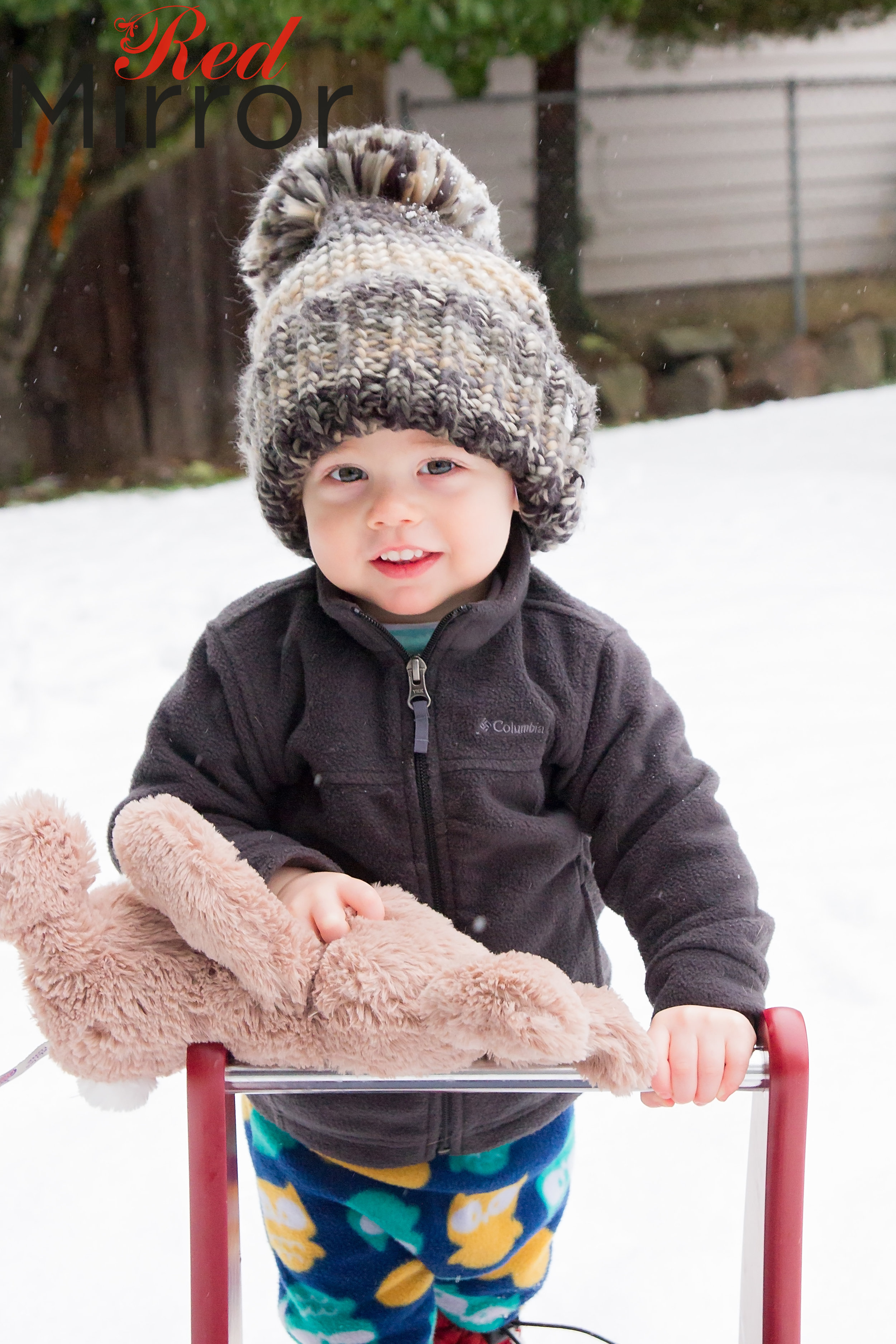 little boy in a big wooly hat, holding a cuddly bunny and a walker