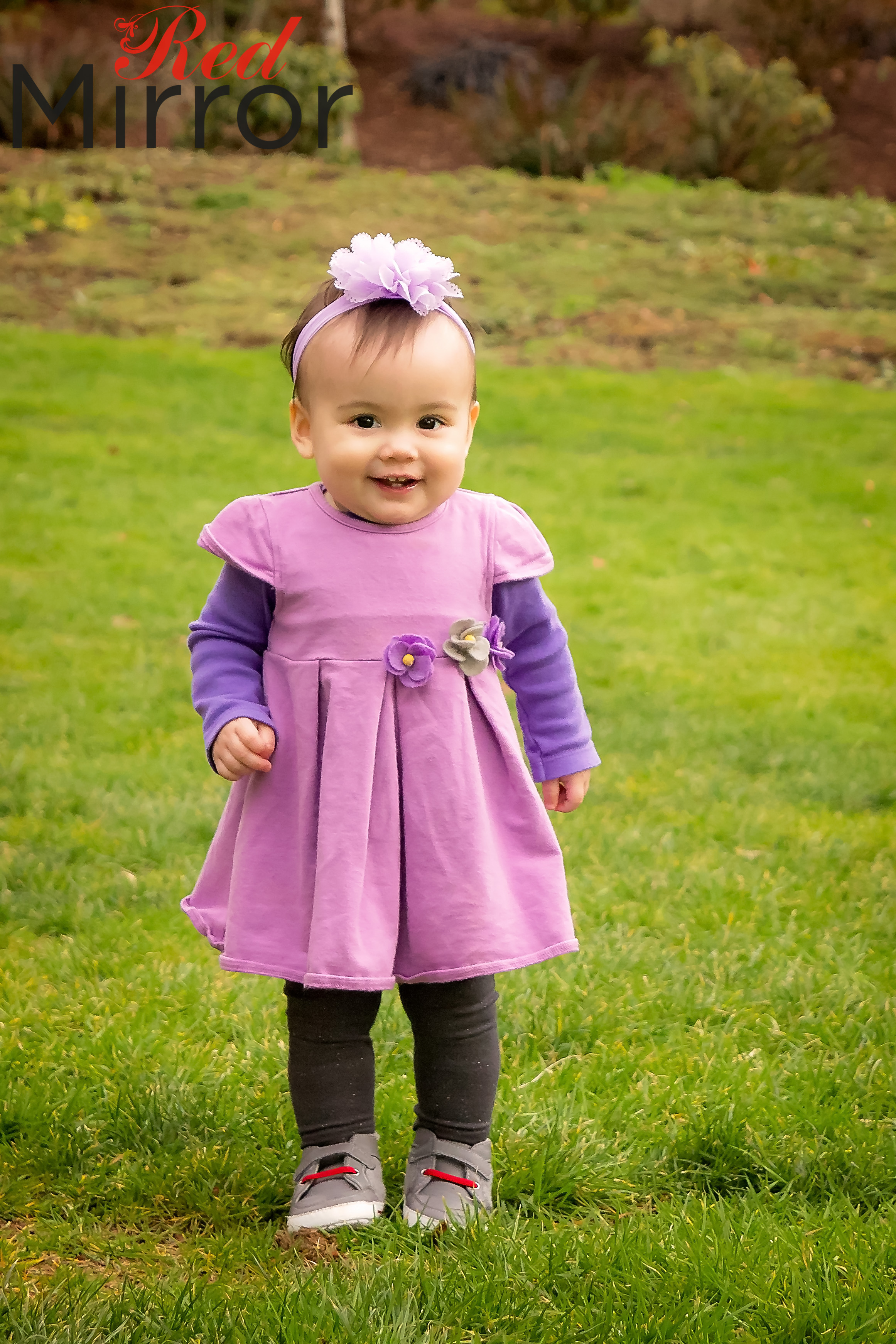 Little girl in a pink and purple dress with a flower headband