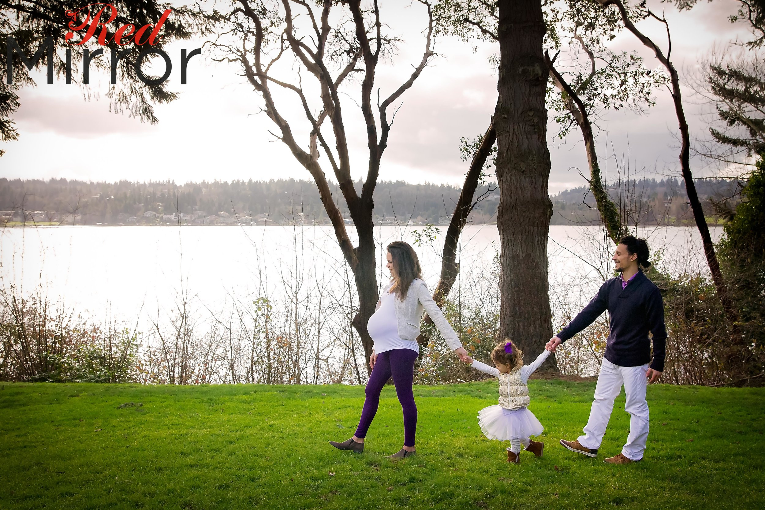 Pregnant woman holding hands with her young daughter who is holding her fathers ahdn. They are walking in a line with a lake behind them