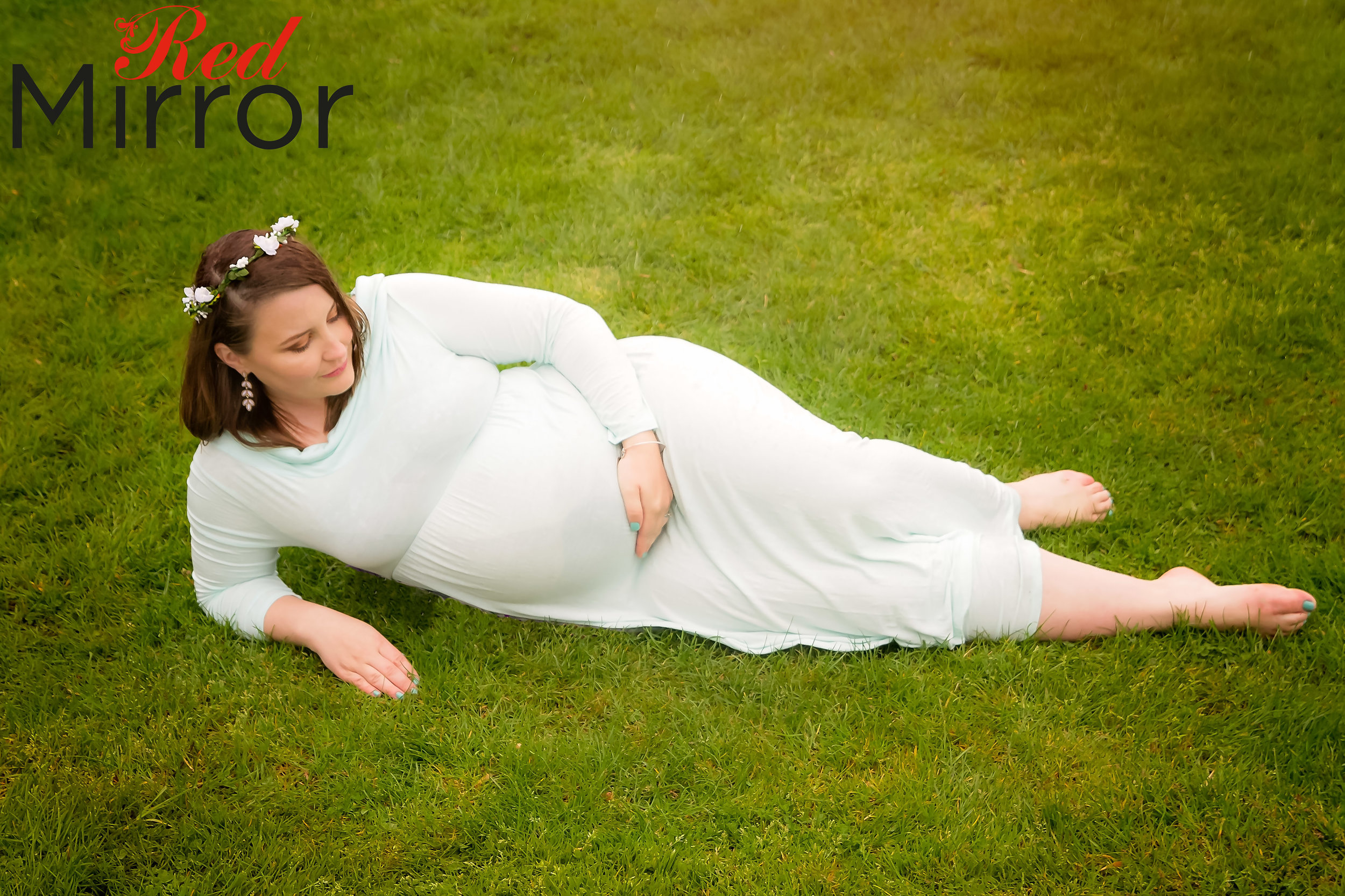 Pregnant woman laying on the grass in a mint color ddress