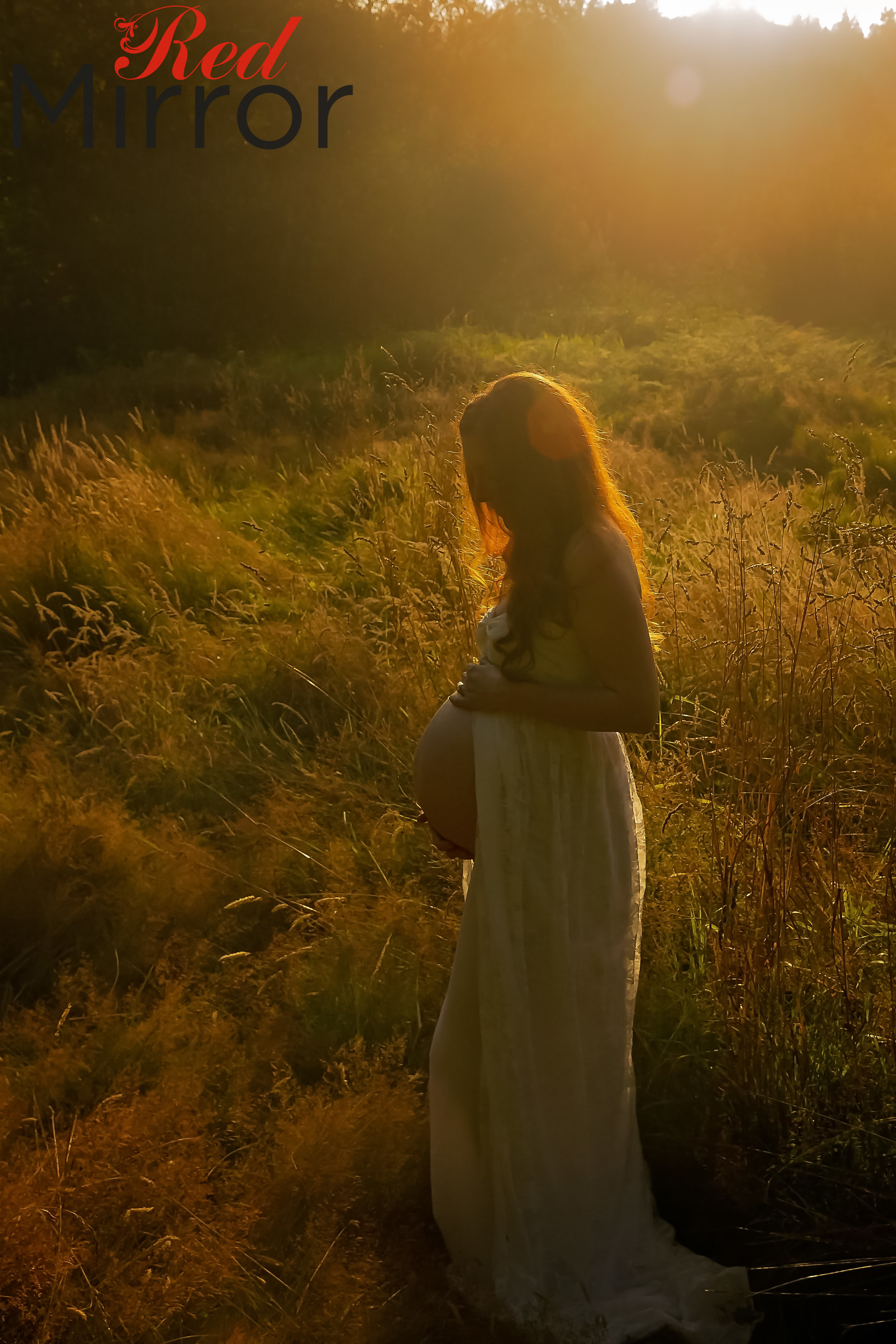 Pregnant woman dressed in open front white lace gown at sunset.