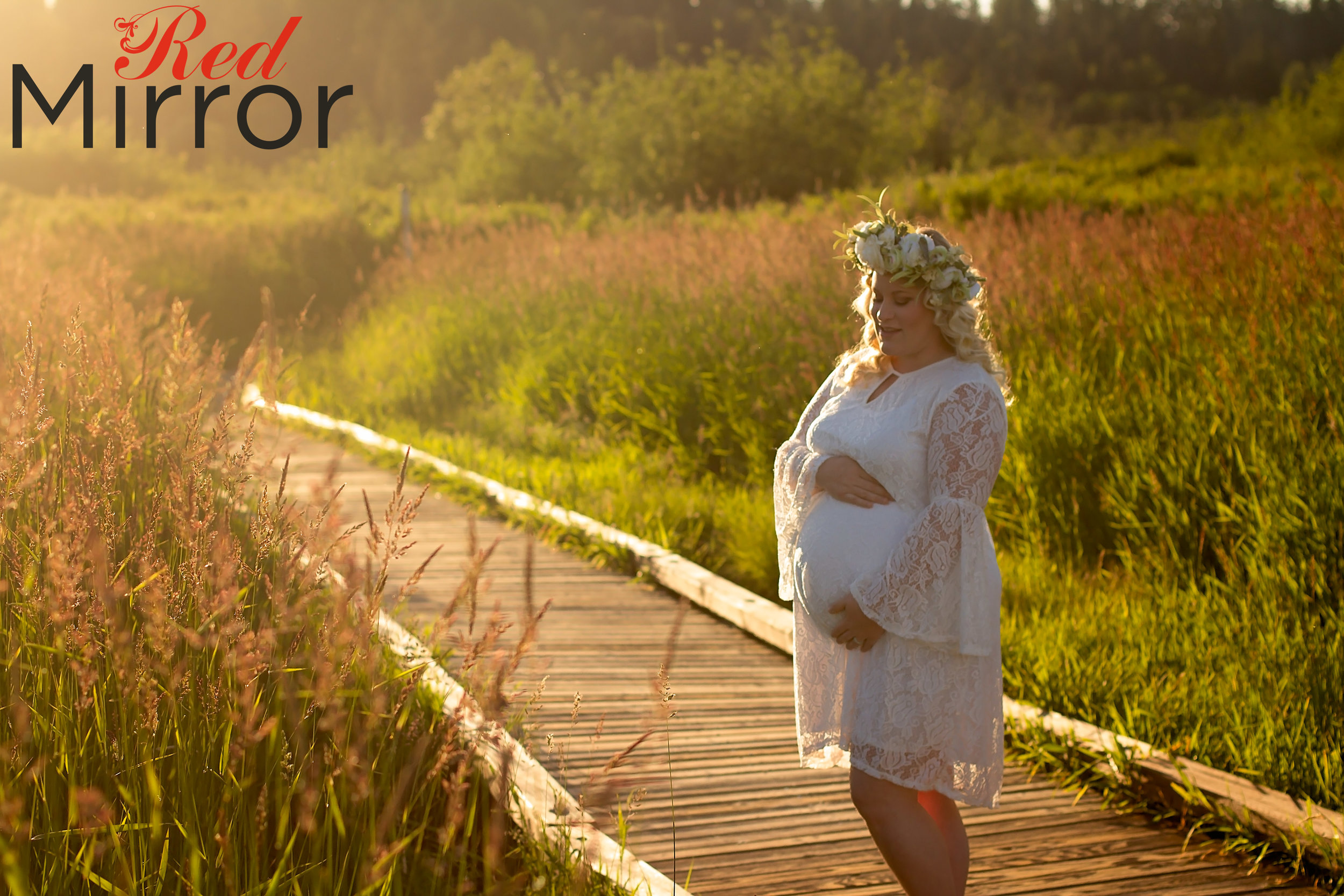 Pregnant woman wearing a flower drown and white lace dress in wetlands at sunset