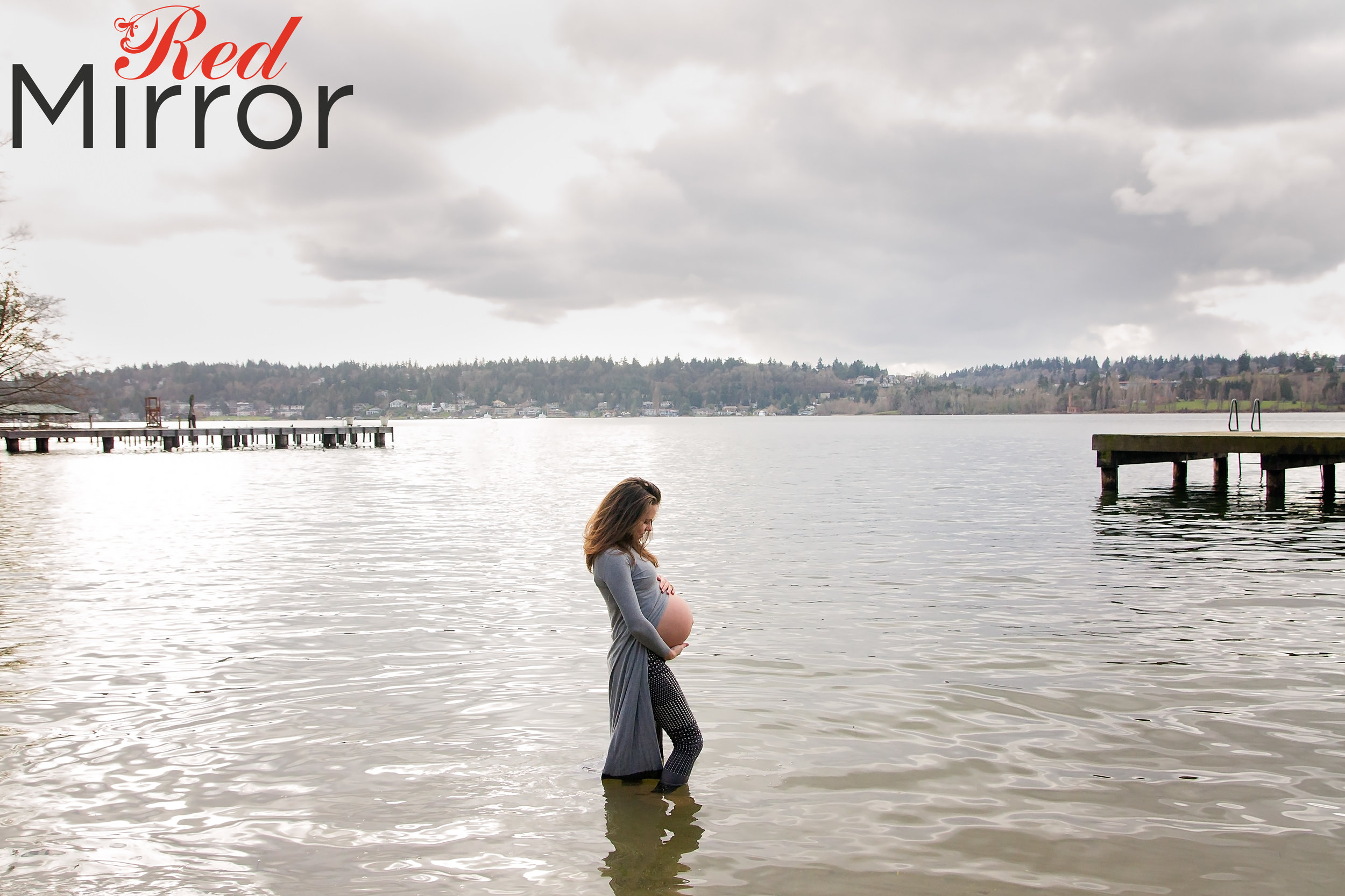 Pregnant woman standing in a lake with an open fronted grey dress with her bump expose.