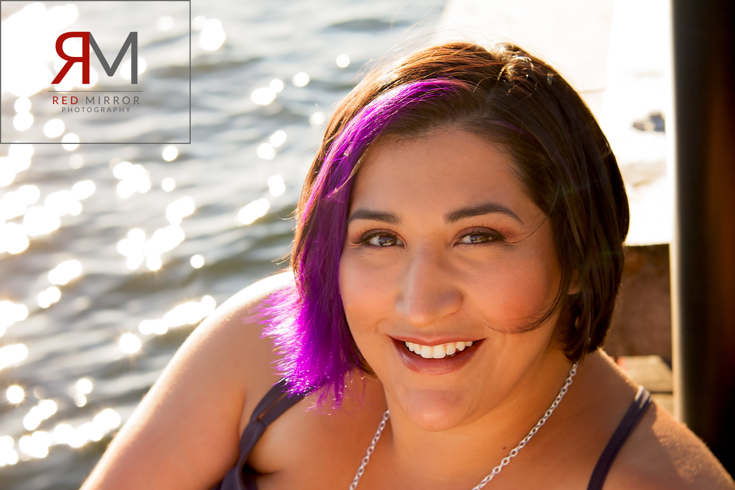 Woman with dark hair and a purple streak smiling in the sun