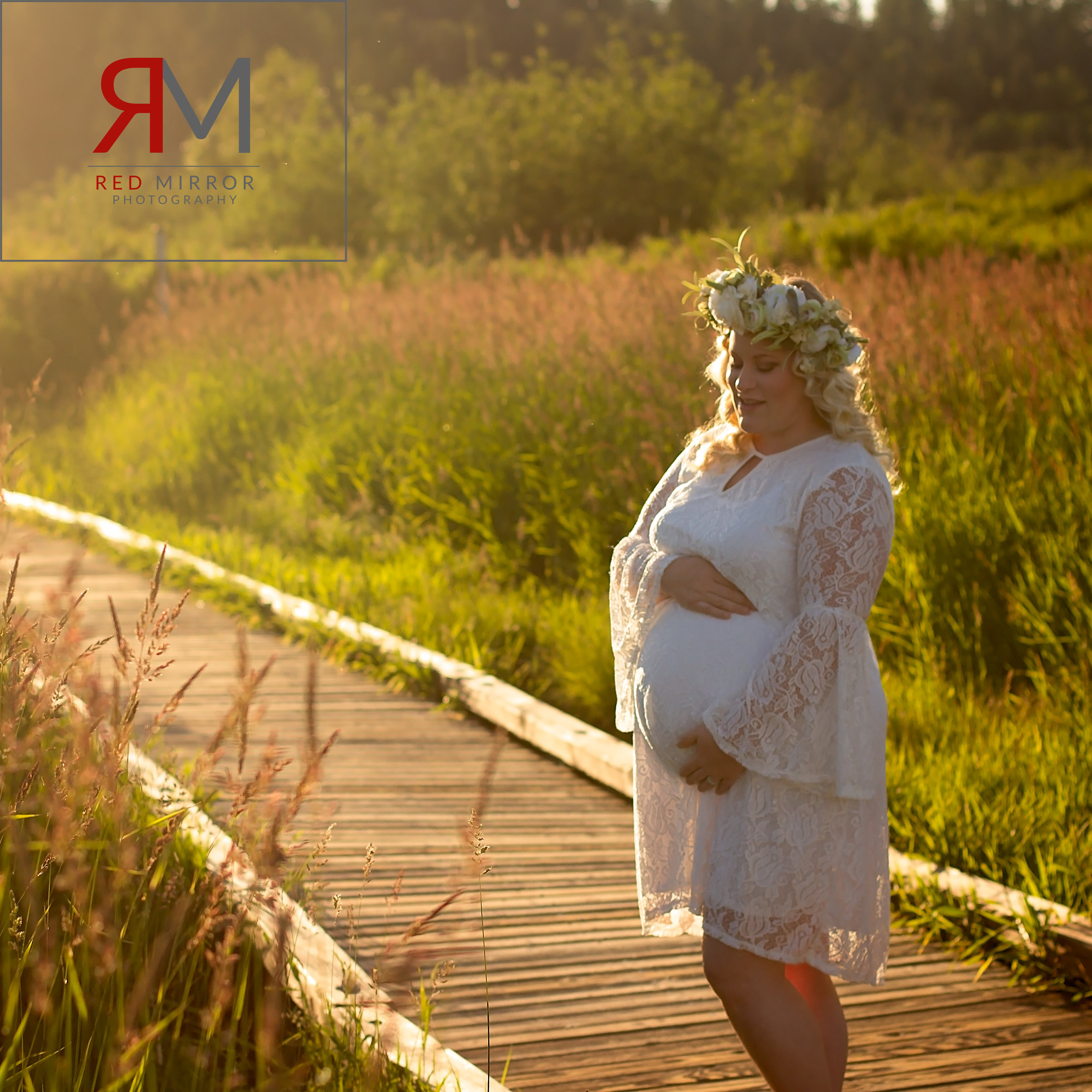 Pregnant woman in a white lace dress in Bothell wetlands at sunset