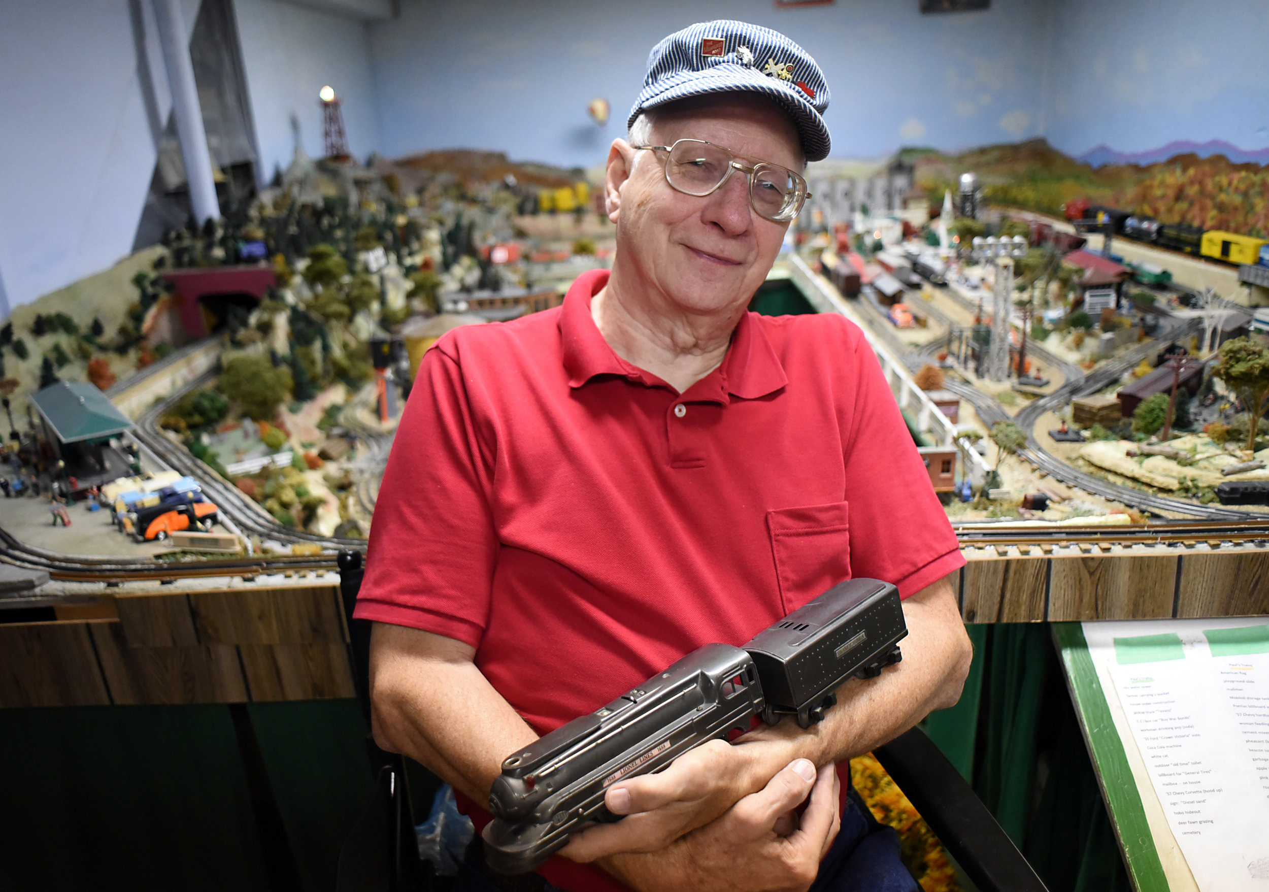 Paul Schoenike holds a Lionel train, given to him by his family doctor in 1940, next to his model train setup in the basement of his home in Monroe Sept. 24, 2015.