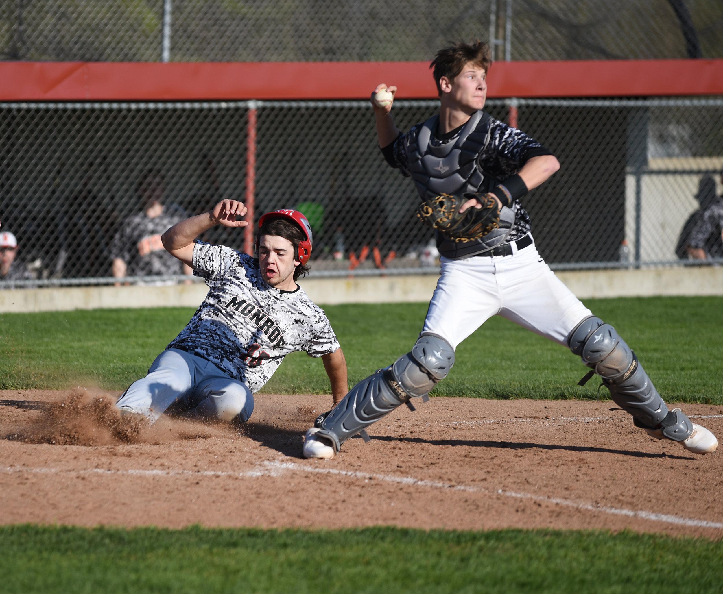 Monroe senior Hogan Edwards slides into home behind Oregon senior catcher Jack Haufle during a game against Oregon at Monroe High School May 5, 2017.