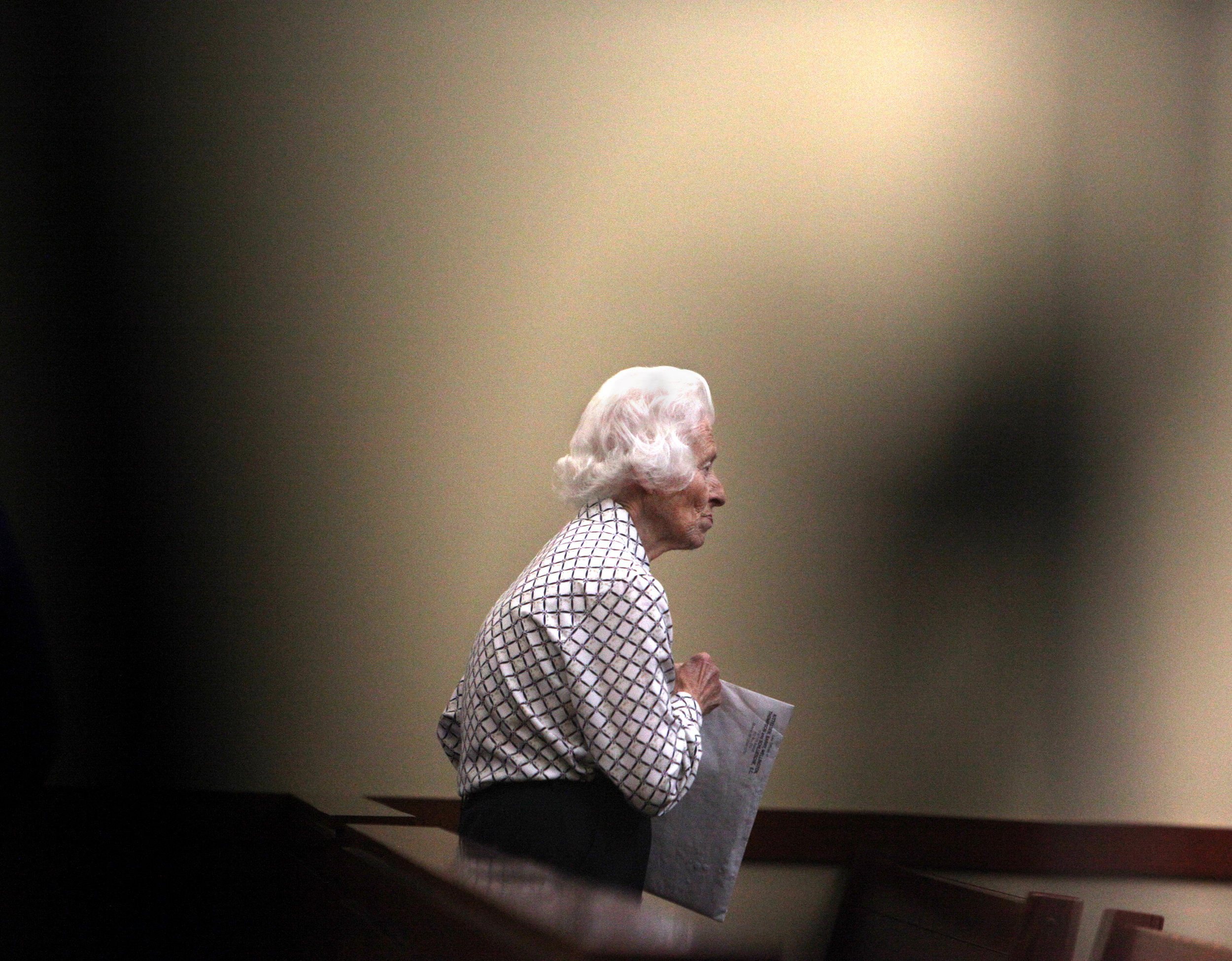 Dolores Marti, 87, walks away while video camera tripods block some of the foreground after her hearing at the Green County Justice Center August 19, 2016. Over 50 cats were seized from Marti's home alive, and 46 were found dead, of which 35 kittens and 6 adult cats were found in a freezer.