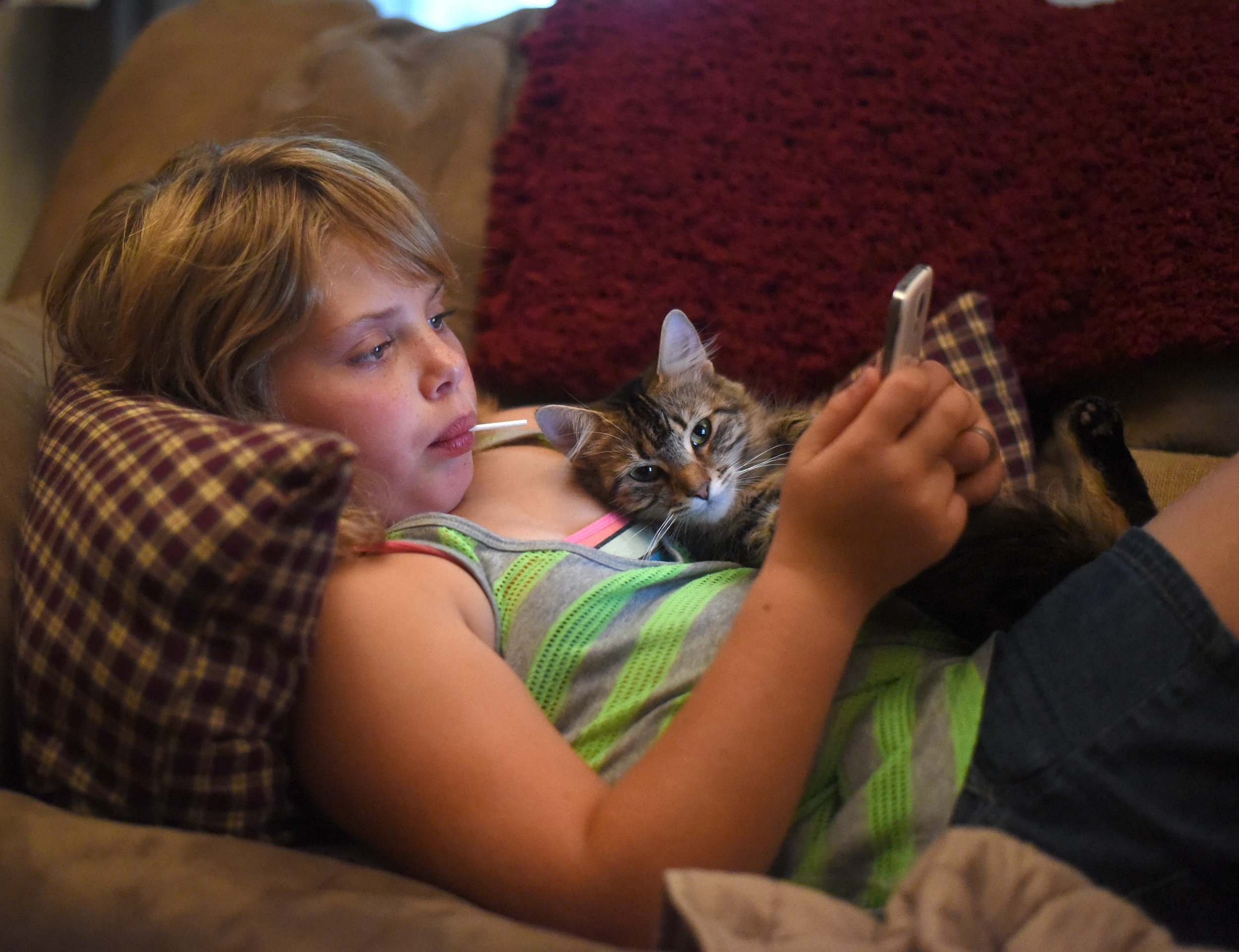 Nine-year-old Alivia Henning, who has autism, lays on her couch with her cat, Elsa, while playing on a cell phone at her home Sept. 22, 2016.